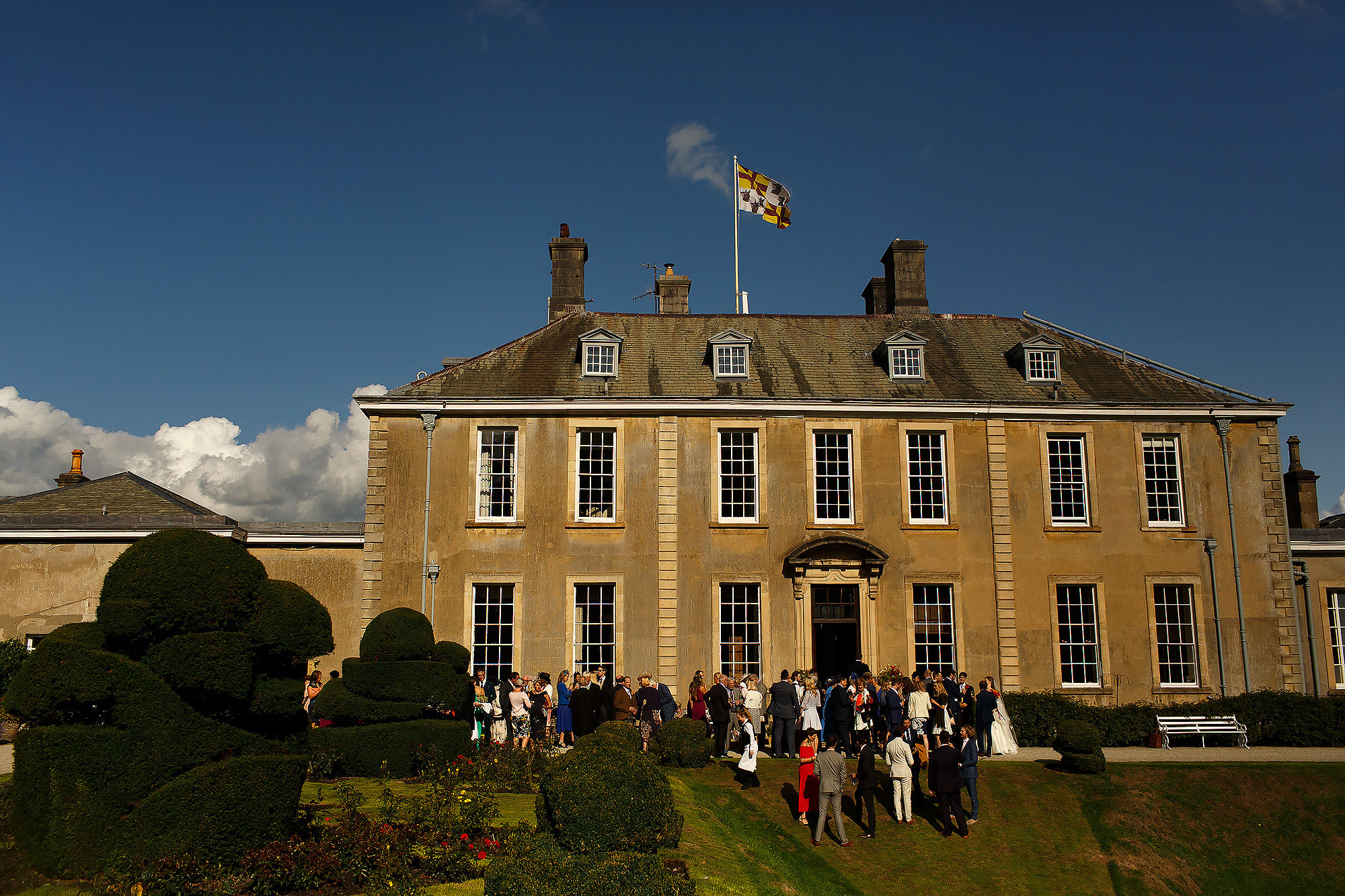 Wedding guests enjoying drinks reception on the lawn of historic lake district building | Lake District Wedding by Toni Darcy Photography