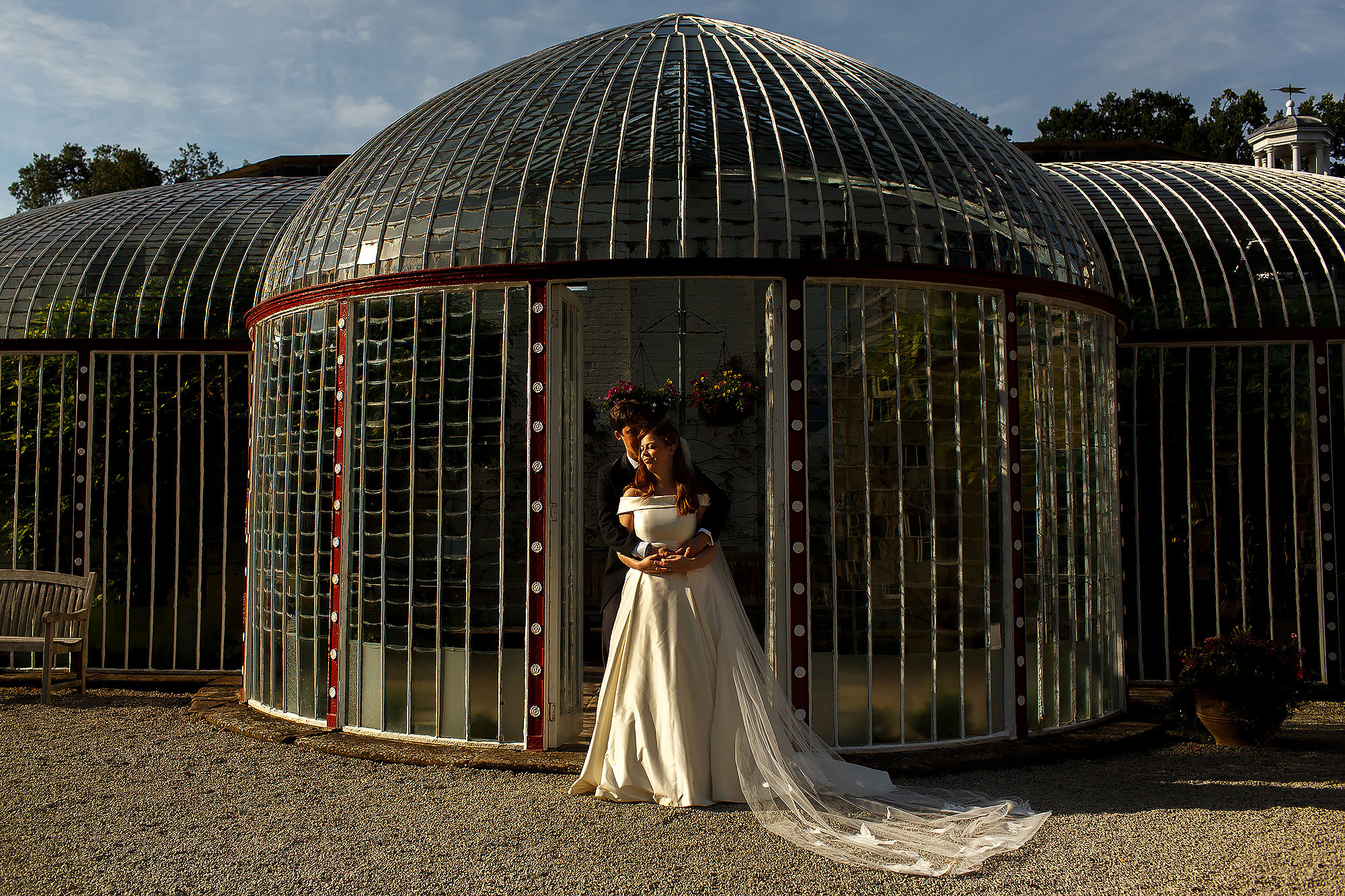 Bride wearing silk off the shoulder wedding dress and groom stood in front of dome glasshouse as the sun shines on them | Lake District Wedding by Toni Darcy Photography