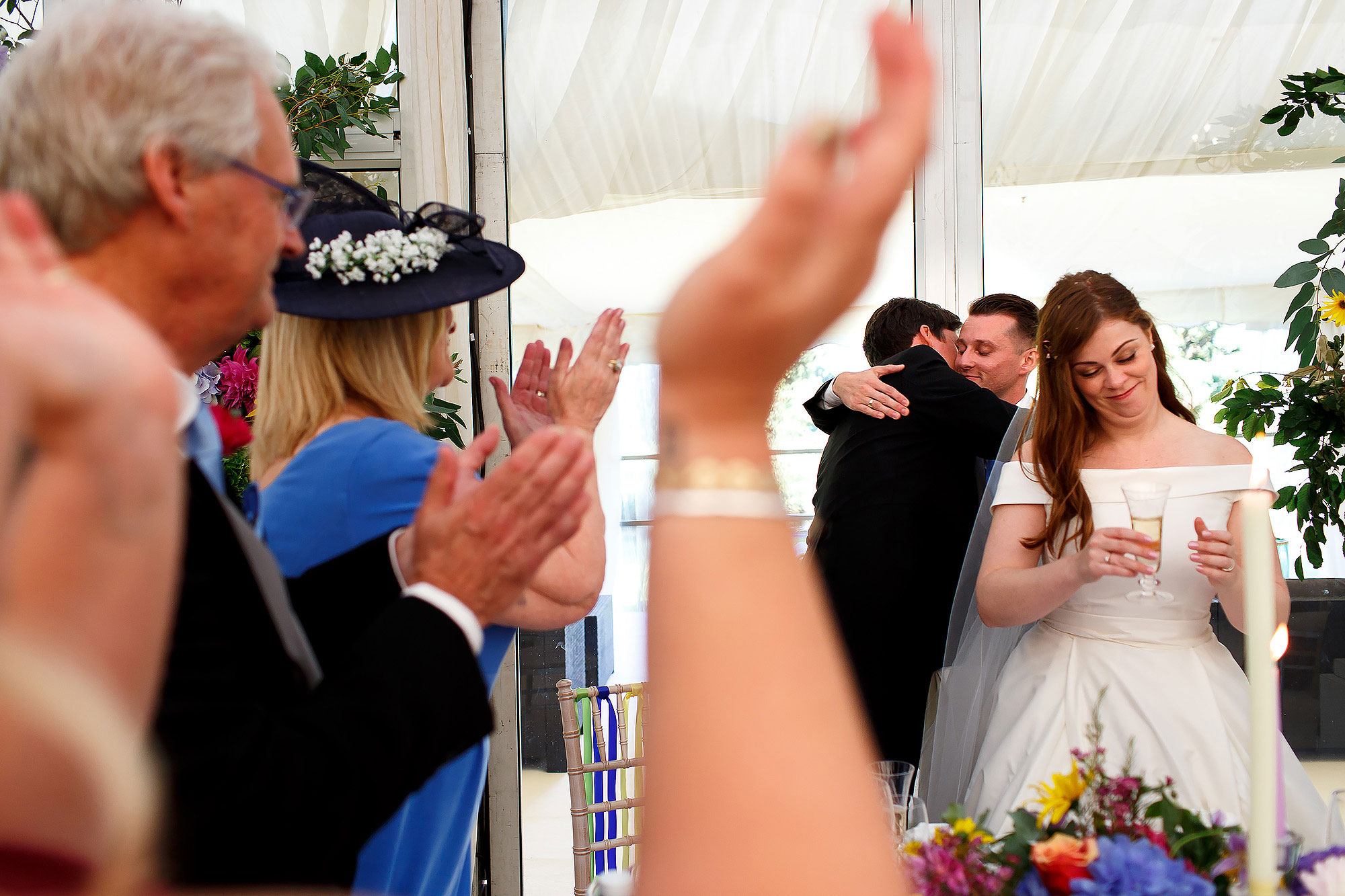 Top table of wedding guests hugging in the marquee wedding reception | Lake District Wedding by Toni Darcy Photography
