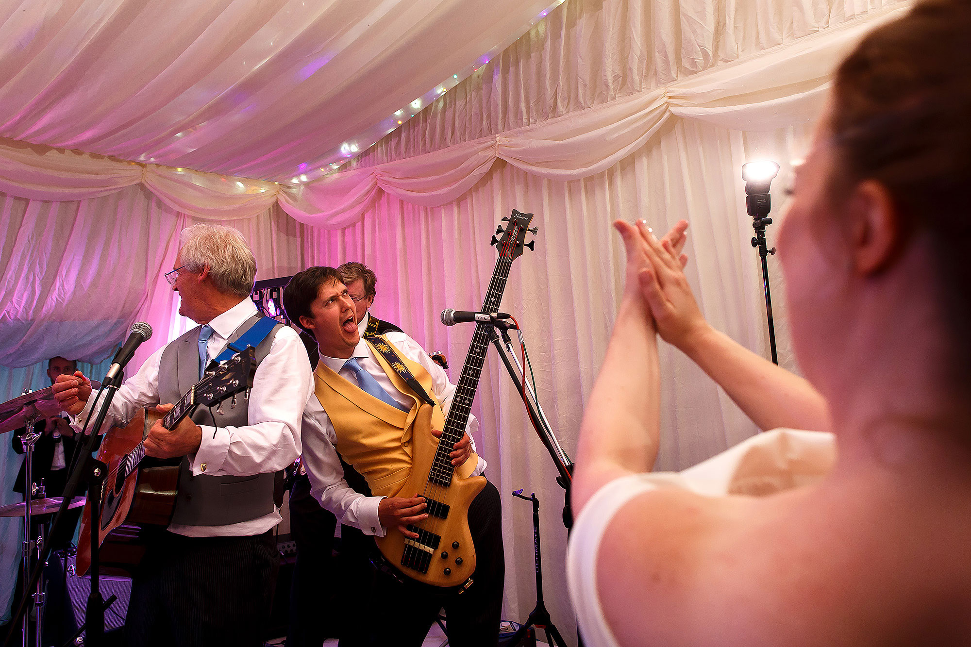 Groom playing the guitar with wedding band as the bride looks on clapping | Lake District Wedding by Toni Darcy Photography