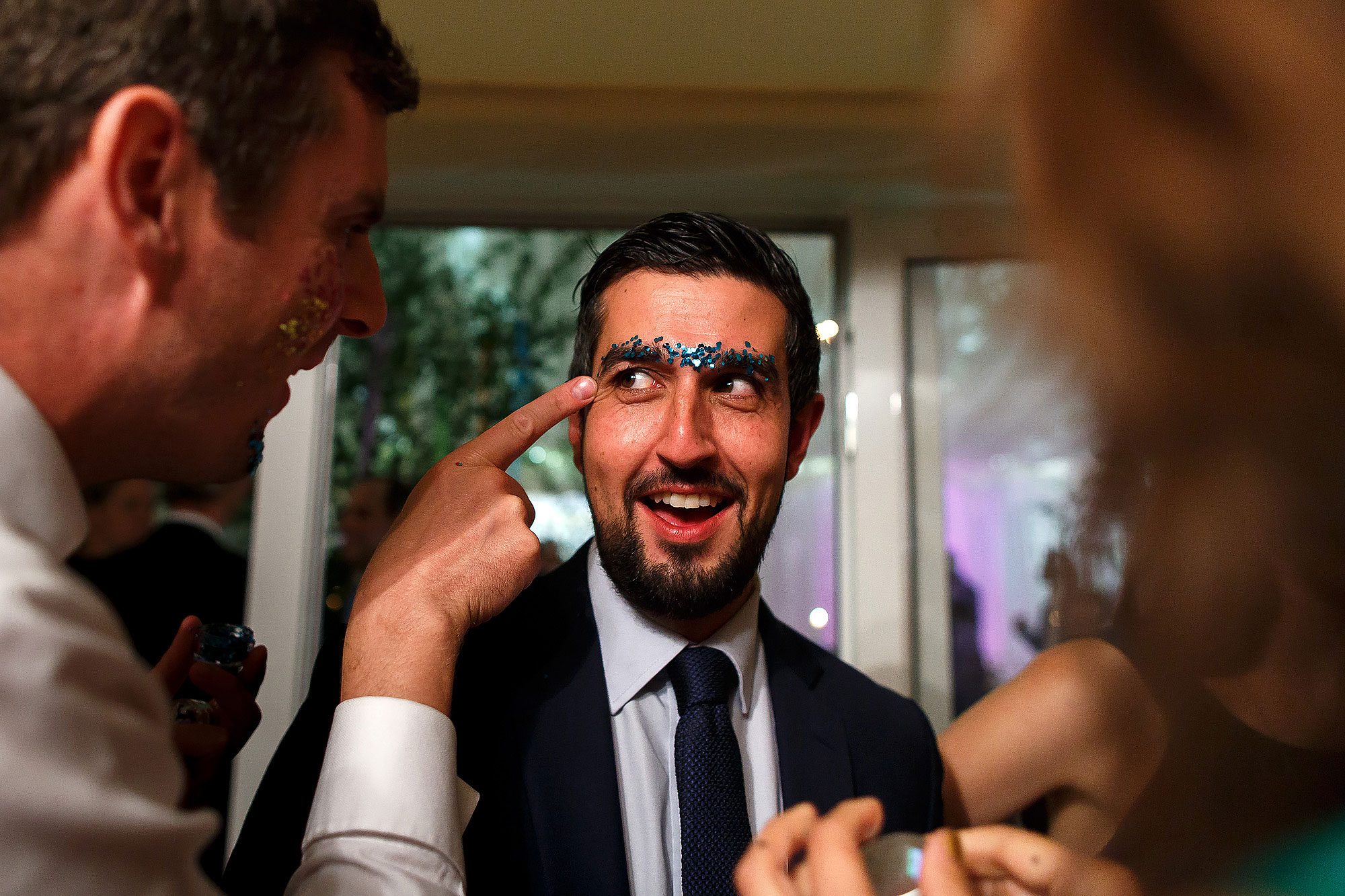 Wedding guests applying glitter paint to eyebrows during wedding reception | Lake District Wedding by Toni Darcy Photography