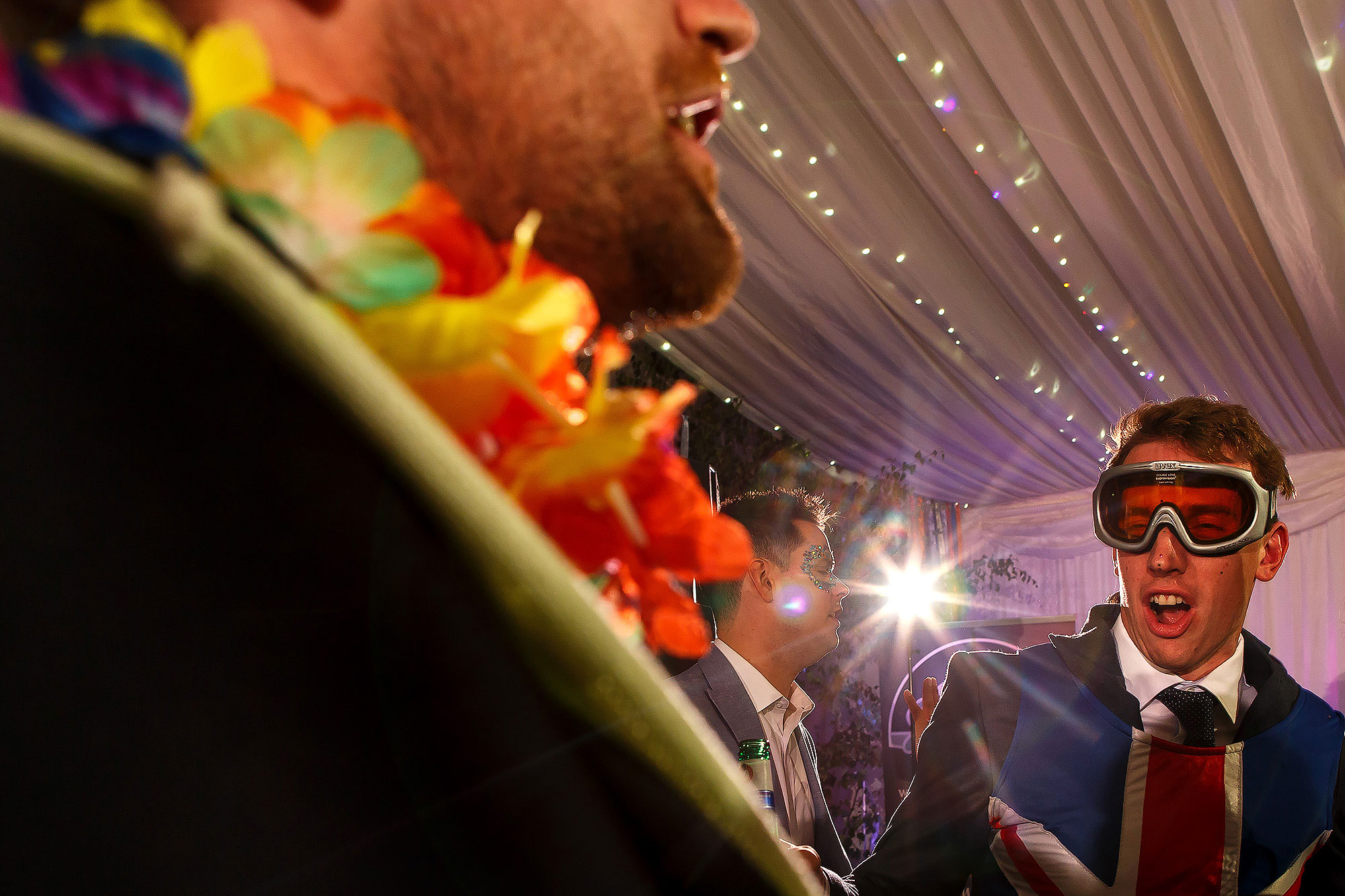 Wedding guests on the marquee dance floor wearing photo booth comedy props | Lake District Wedding by Toni Darcy Photography