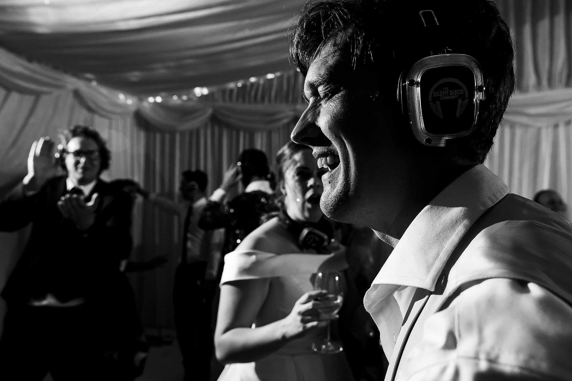 Wedding guests throwing their arms in the air wearing silent disco ear phones for wedding party in marquee Lake District Wedding by Toni Darcy Photography
