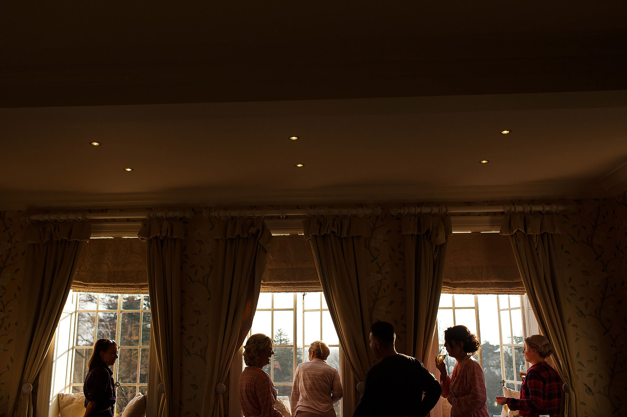 All the bridesmaids looking out the windows of the bridal suite | Eaves Hall wedding photography by Toni Darcy