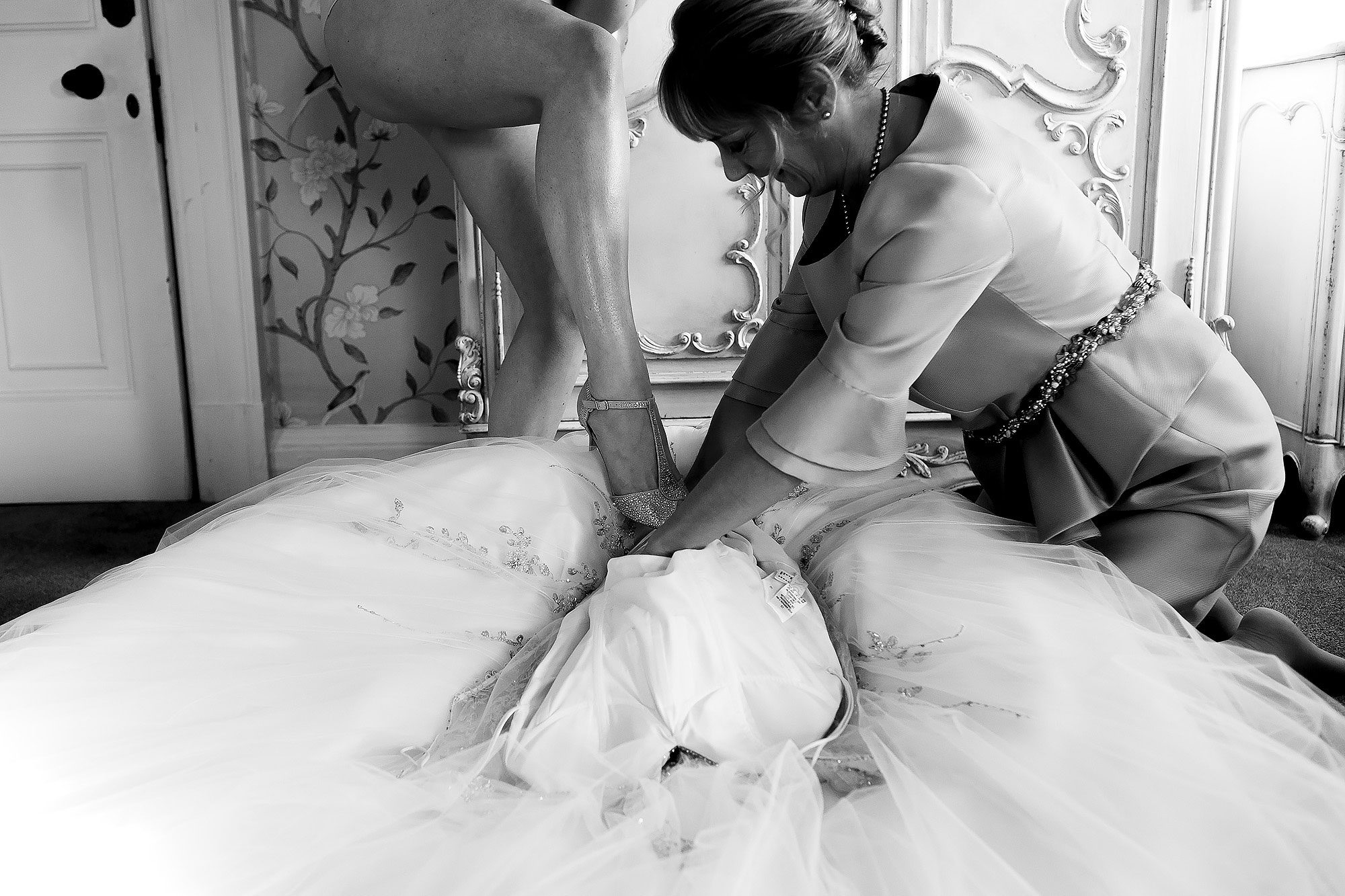 Brides naked leg wearing wedding shoes as she steps into her wedding dress | Eaves Hall wedding photography by Toni Darcy