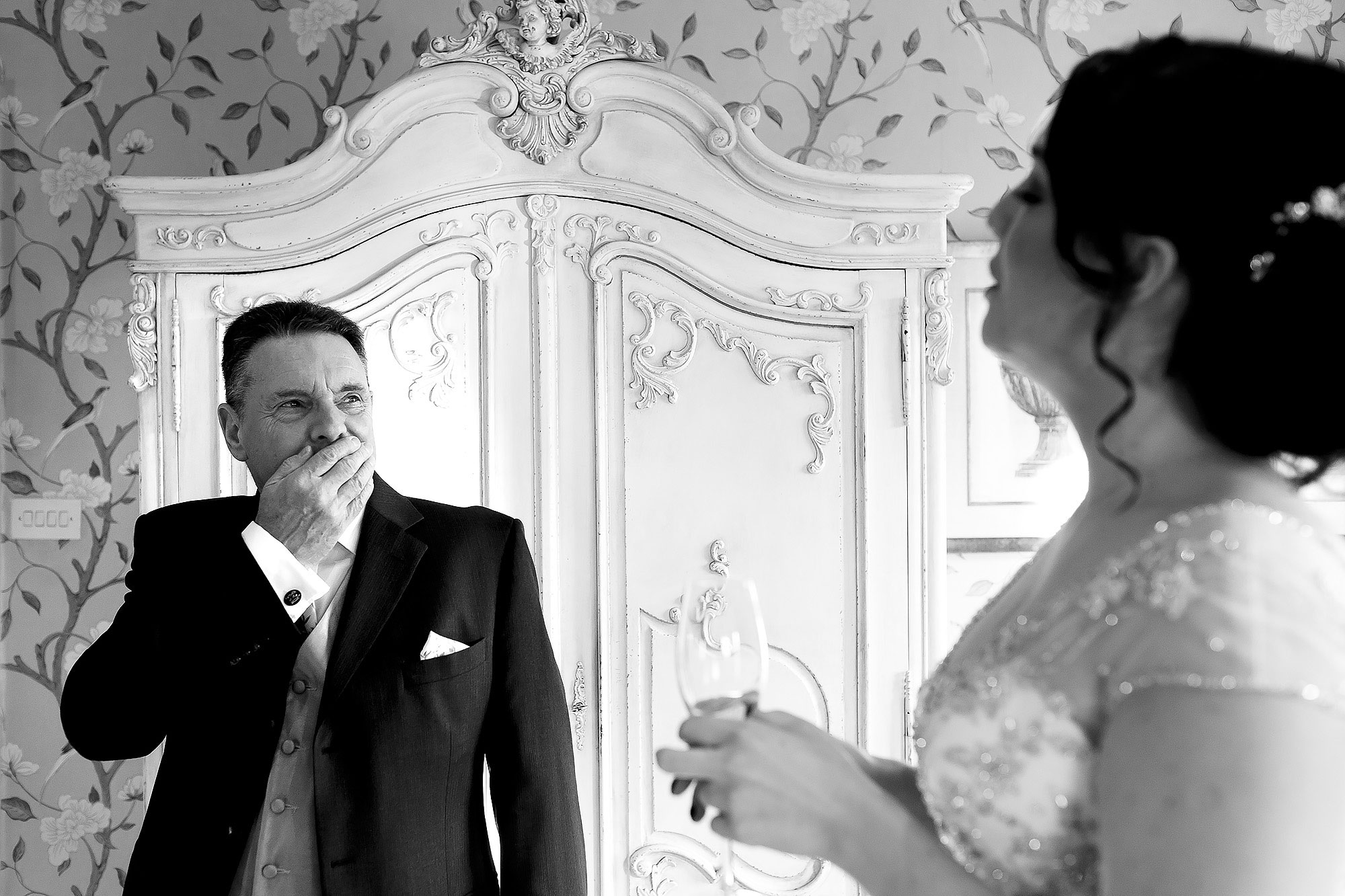 Father of the brides holding his hand to his face as he sees his daughter in her wedding dress for the first time | Eaves Hall wedding photography by Toni Darcy
