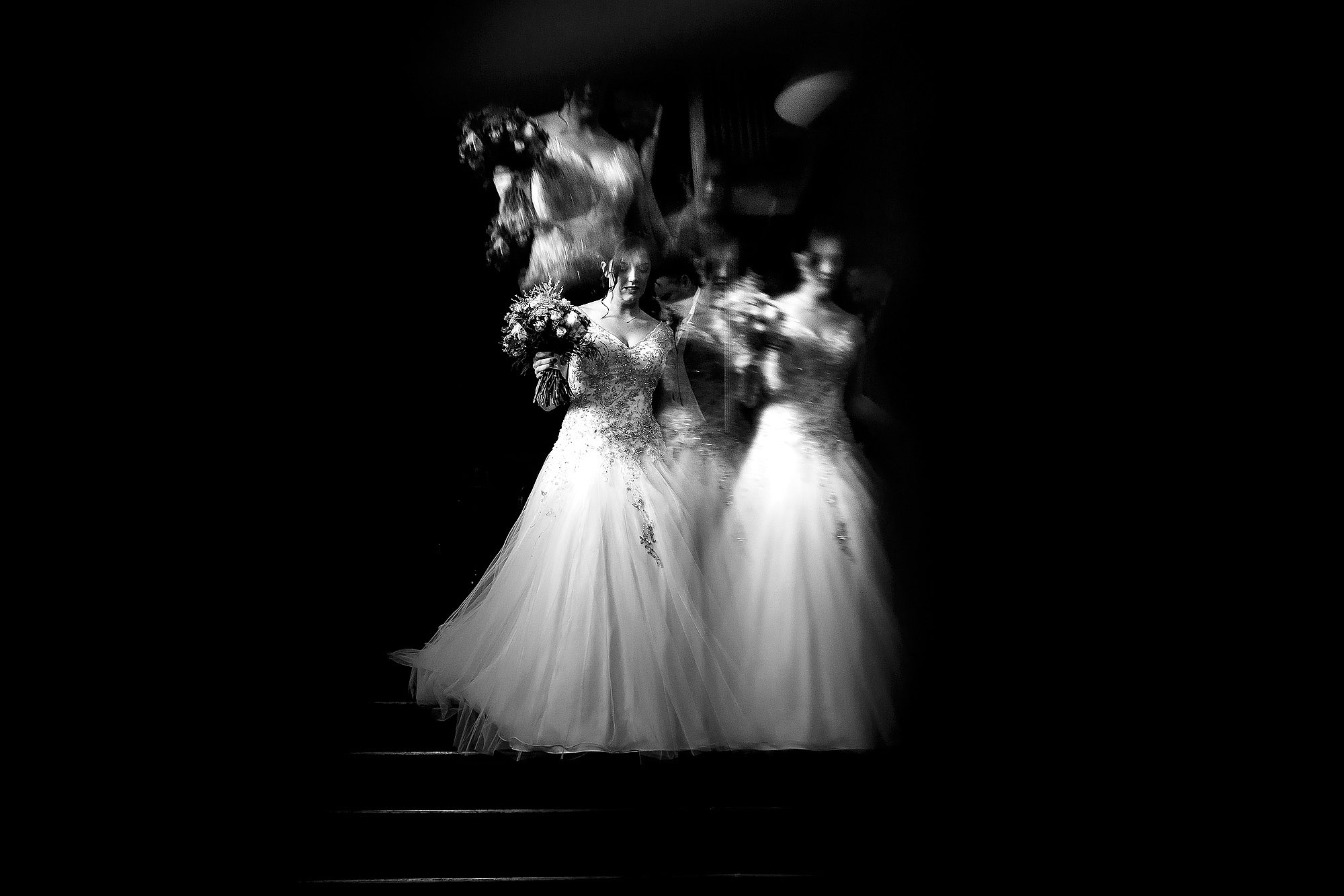 Bride walking down the staircase holding her wedding bouquet | Eaves Hall wedding photography by Toni Darcy