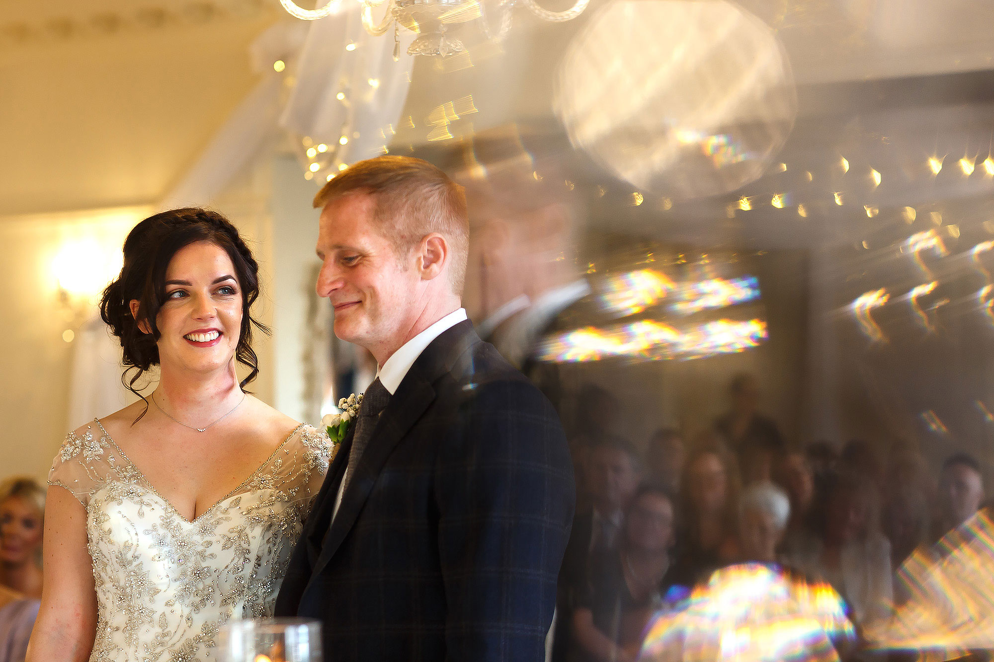 Bride with dark hair and low bun wearing beaded wedding dress smiling, looking towards the groom | Eaves Hall wedding photography by Toni Darcy