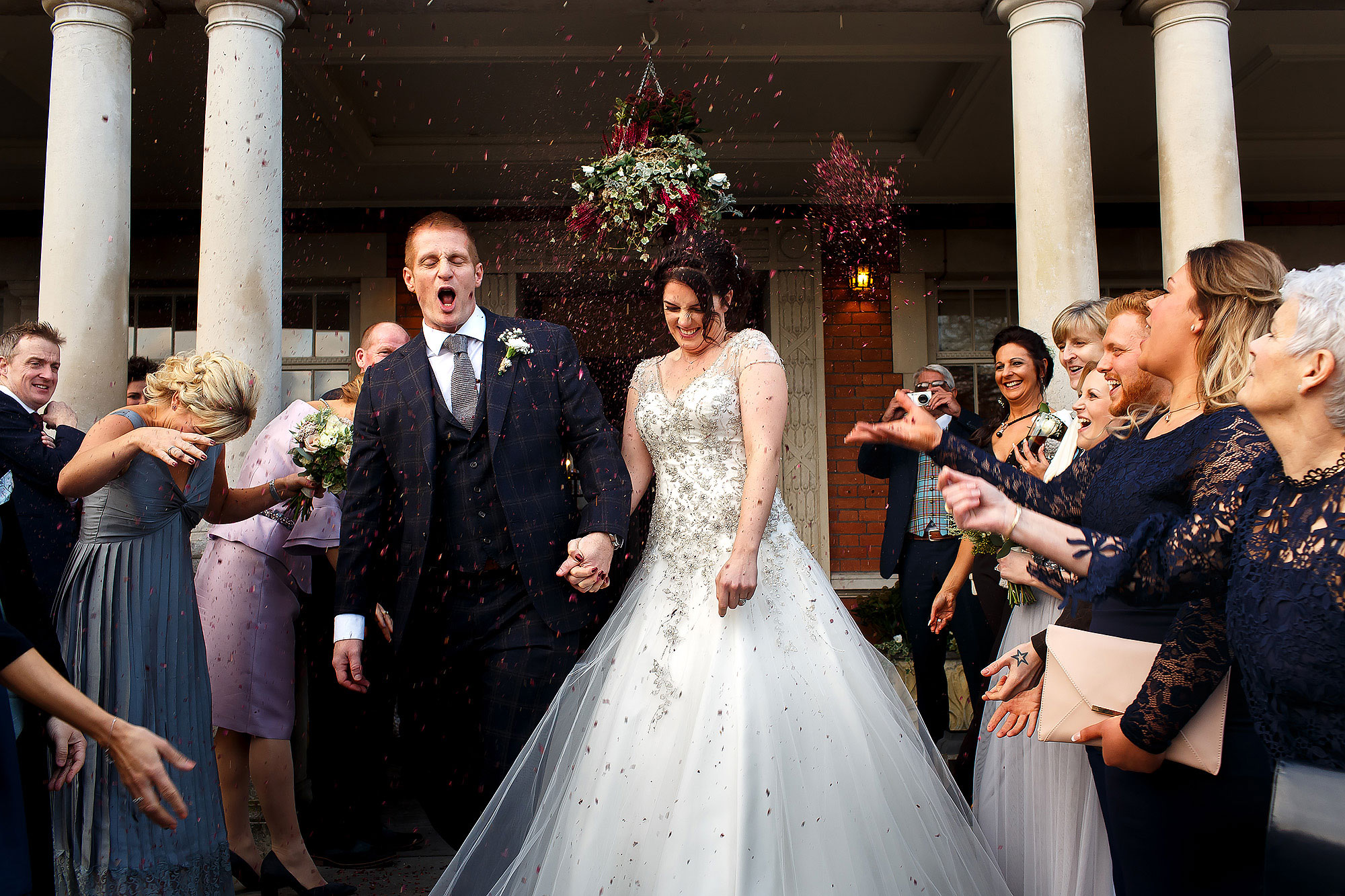 Bride and groom walking out of the pillared entrance as wedding guests throw deep red confetti | Eaves Hall wedding photography by Toni Darcy
