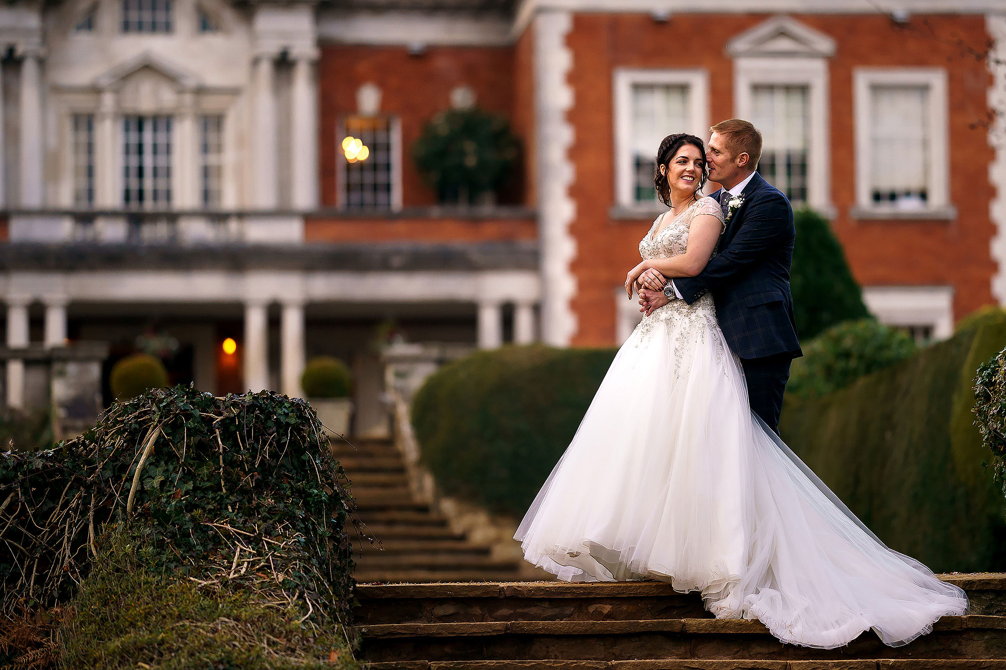 Bride and groom stood hugging on the steps in the gardens of Eaves Hall with the red brick building in the background | Eaves Hall wedding photography by Toni Darcy