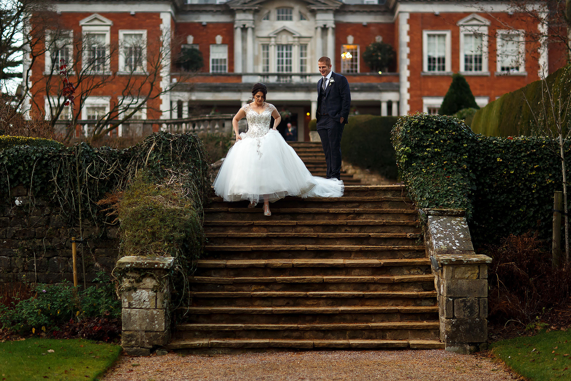 Bride walking into the gardens holding her dress as she walks down the steps with Eaves Hall in the background | Eaves Hall wedding photography by Toni Darcy