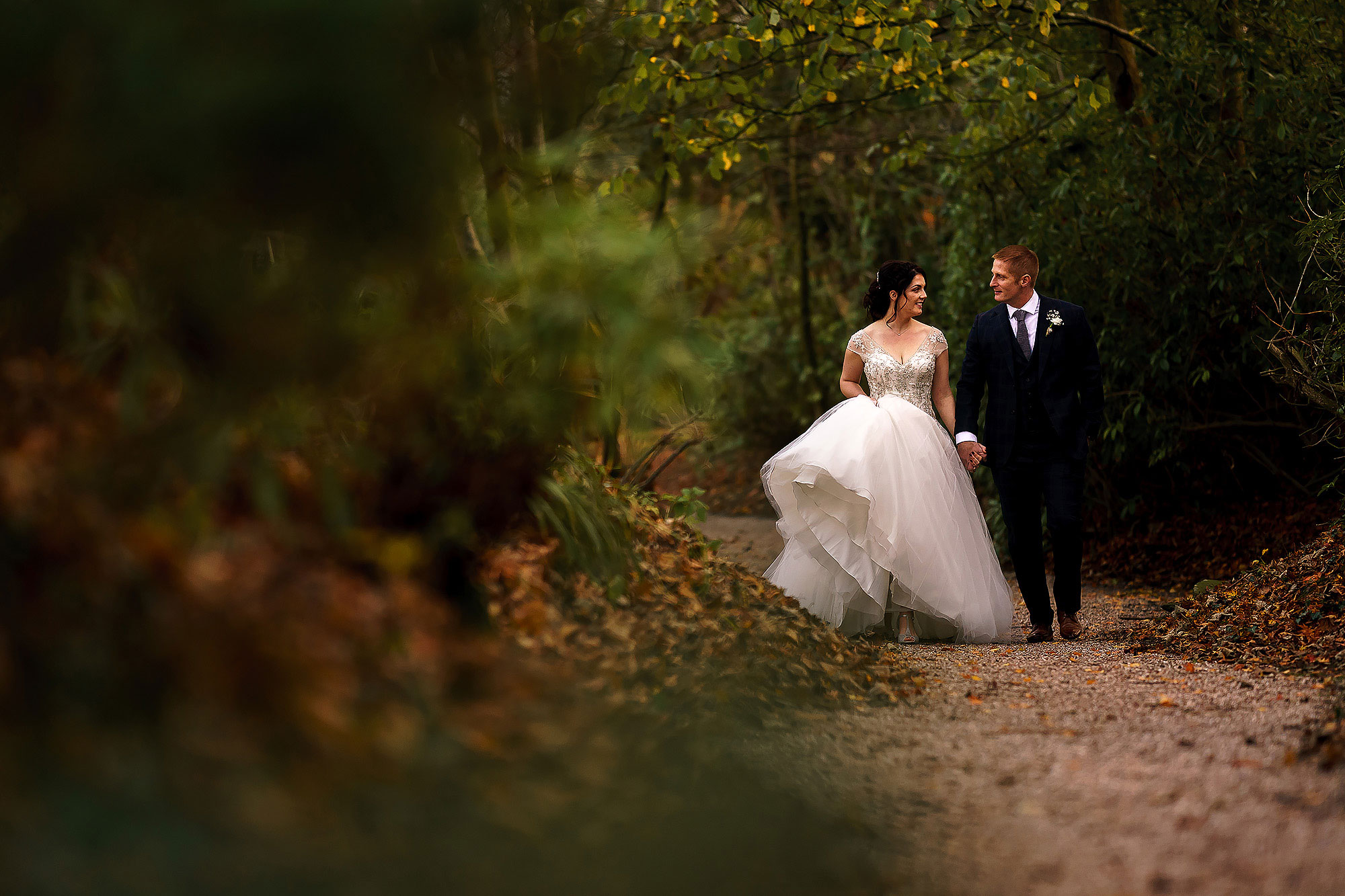 Bride and groom walking down the path way through the trees hand in hand | Eaves Hall wedding photography by Toni Darcy