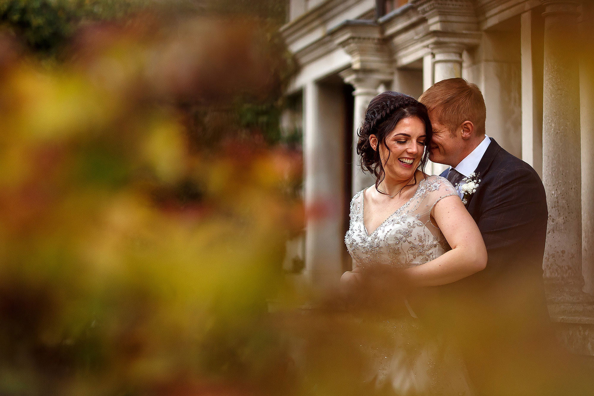 Bride and groom laughing in each others arms in the gardens | Eaves Hall wedding photography by Toni Darcy