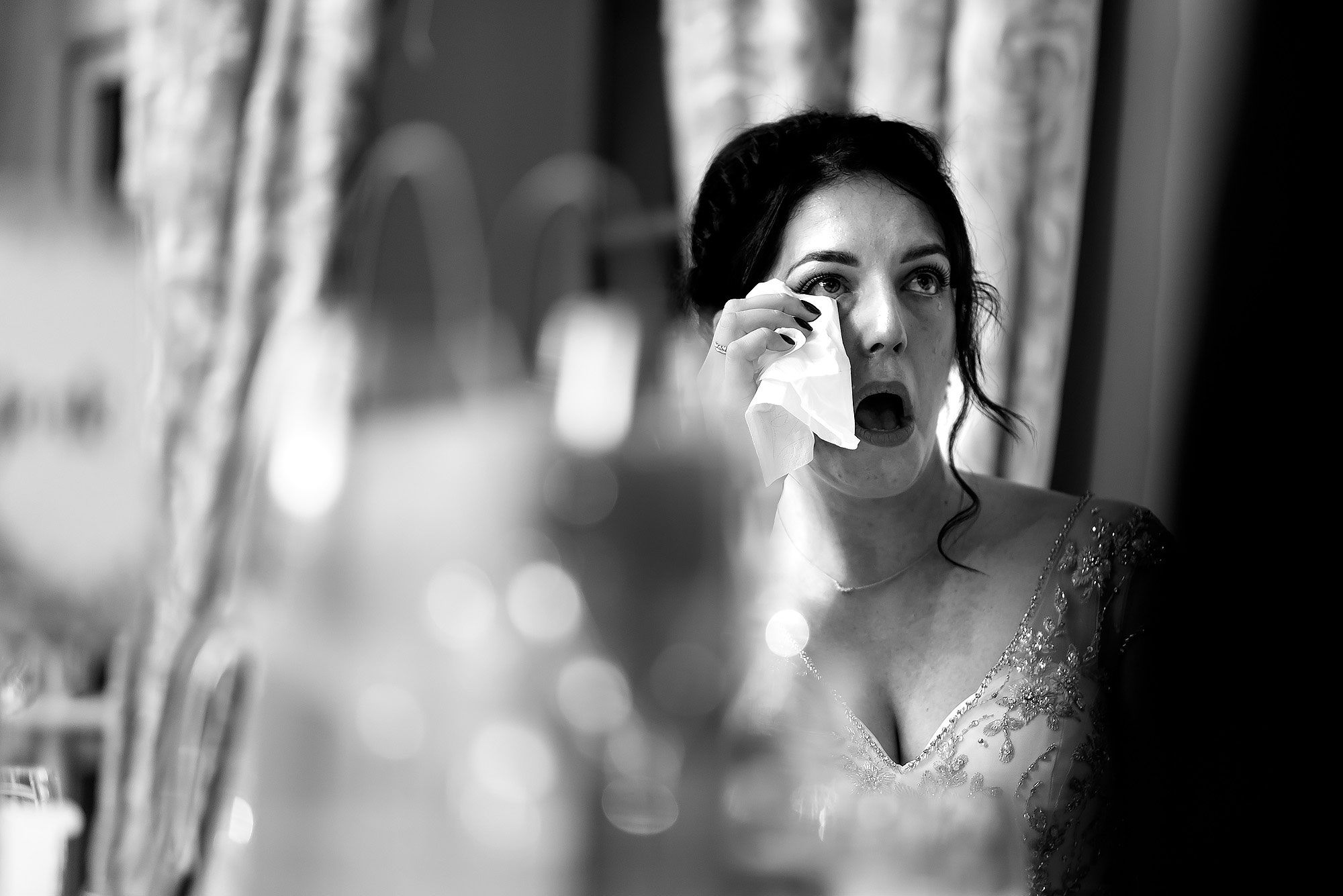 Bride holding a tissue to her eye as she feels emotional during the wedding speeches | Eaves Hall wedding photography by Toni Darcy