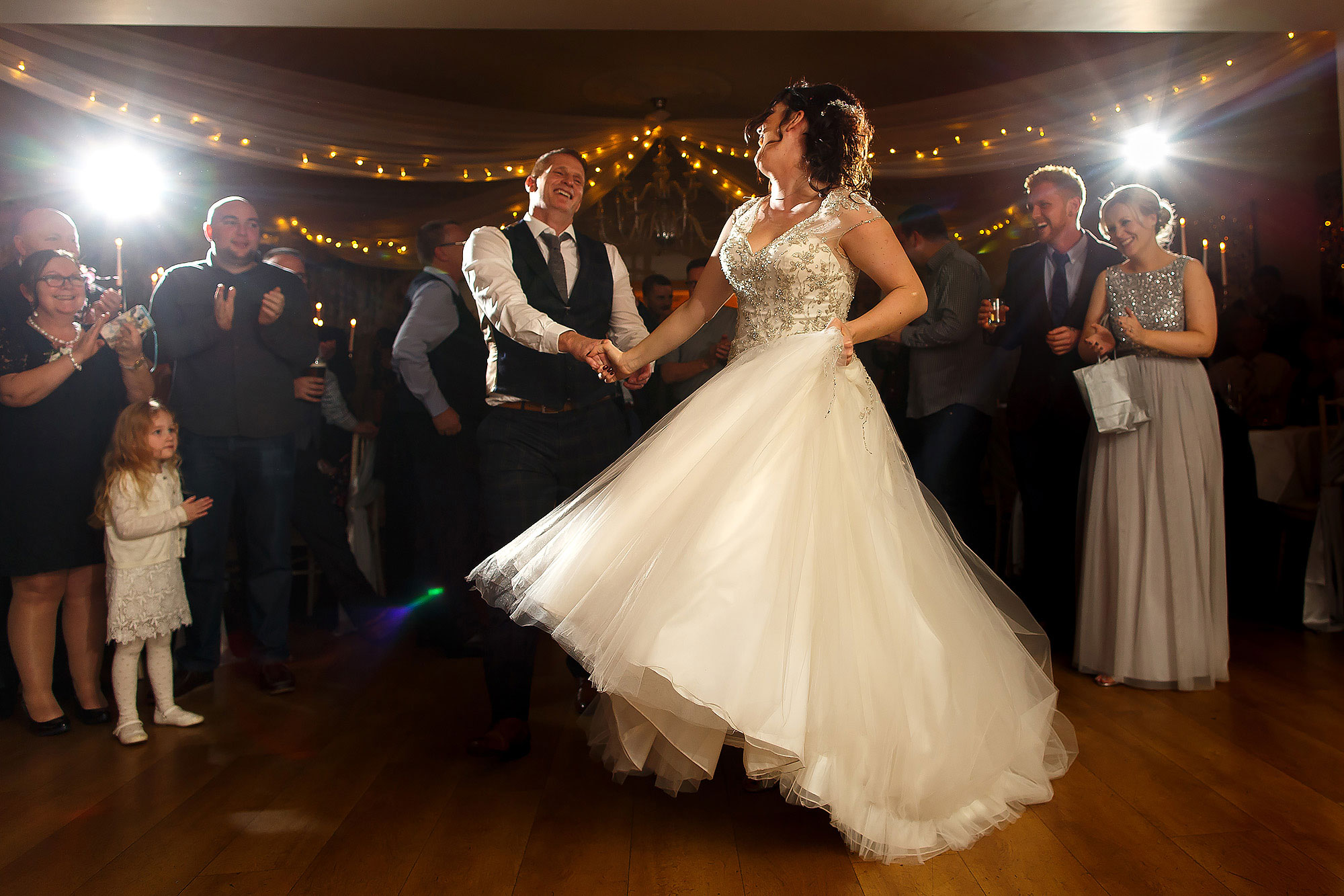 Bride and groom swinging each other round the dance floor with the wedding dress flowing | Eaves Hall wedding photography by Toni Darcy