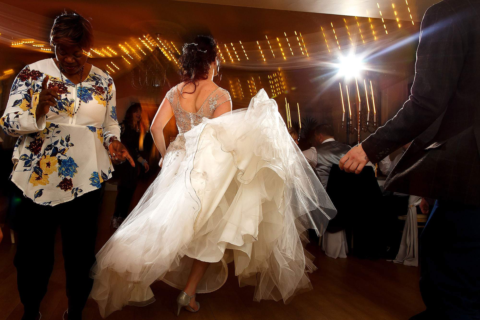 Bride throwing her wedding dress round the dance floor as she dances with wedding guests | Eaves Hall wedding photography by Toni Darcy