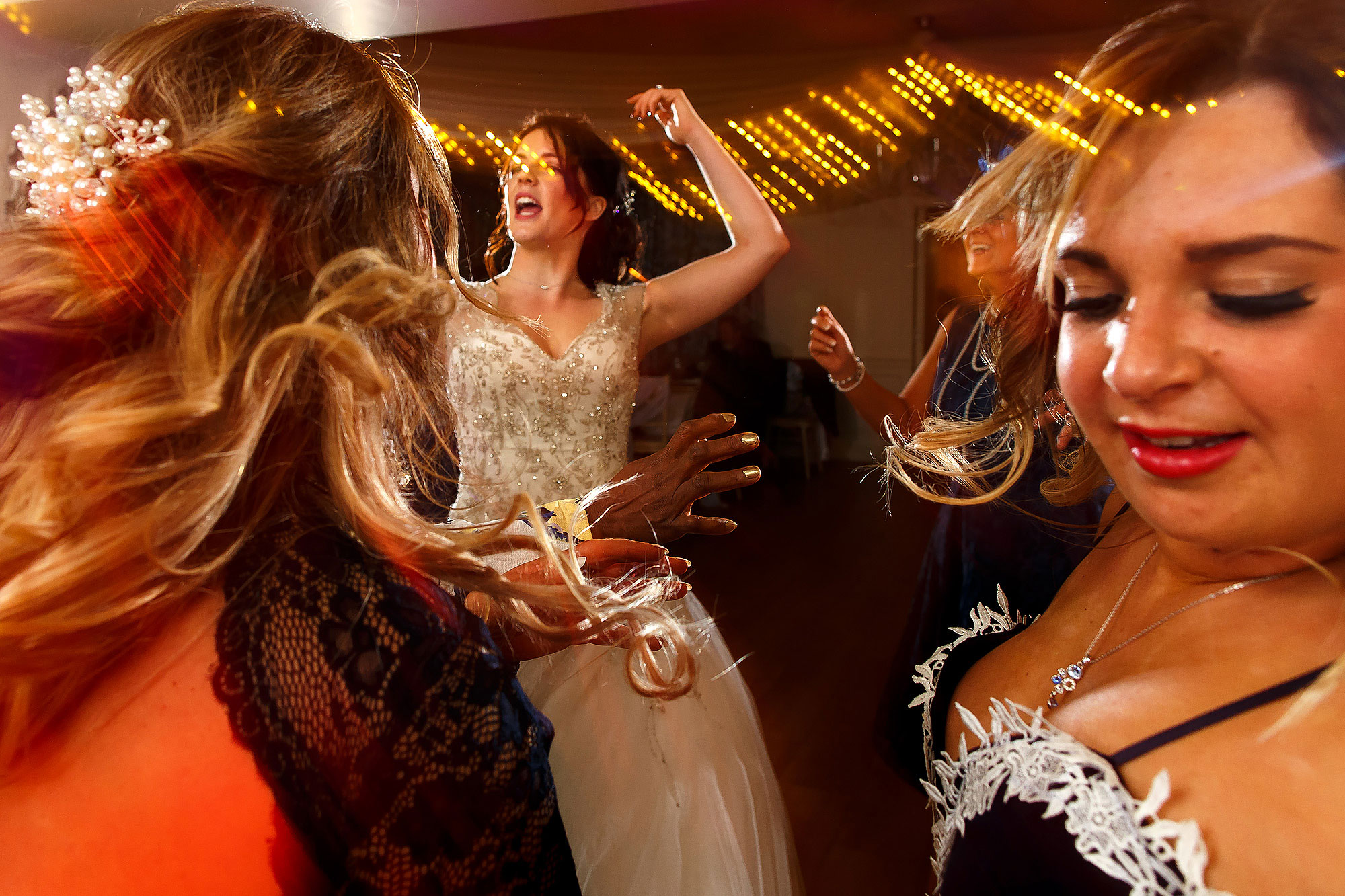 Wedding guests partying on the dance floor with light trails | Eaves Hall wedding photography by Toni Darcy