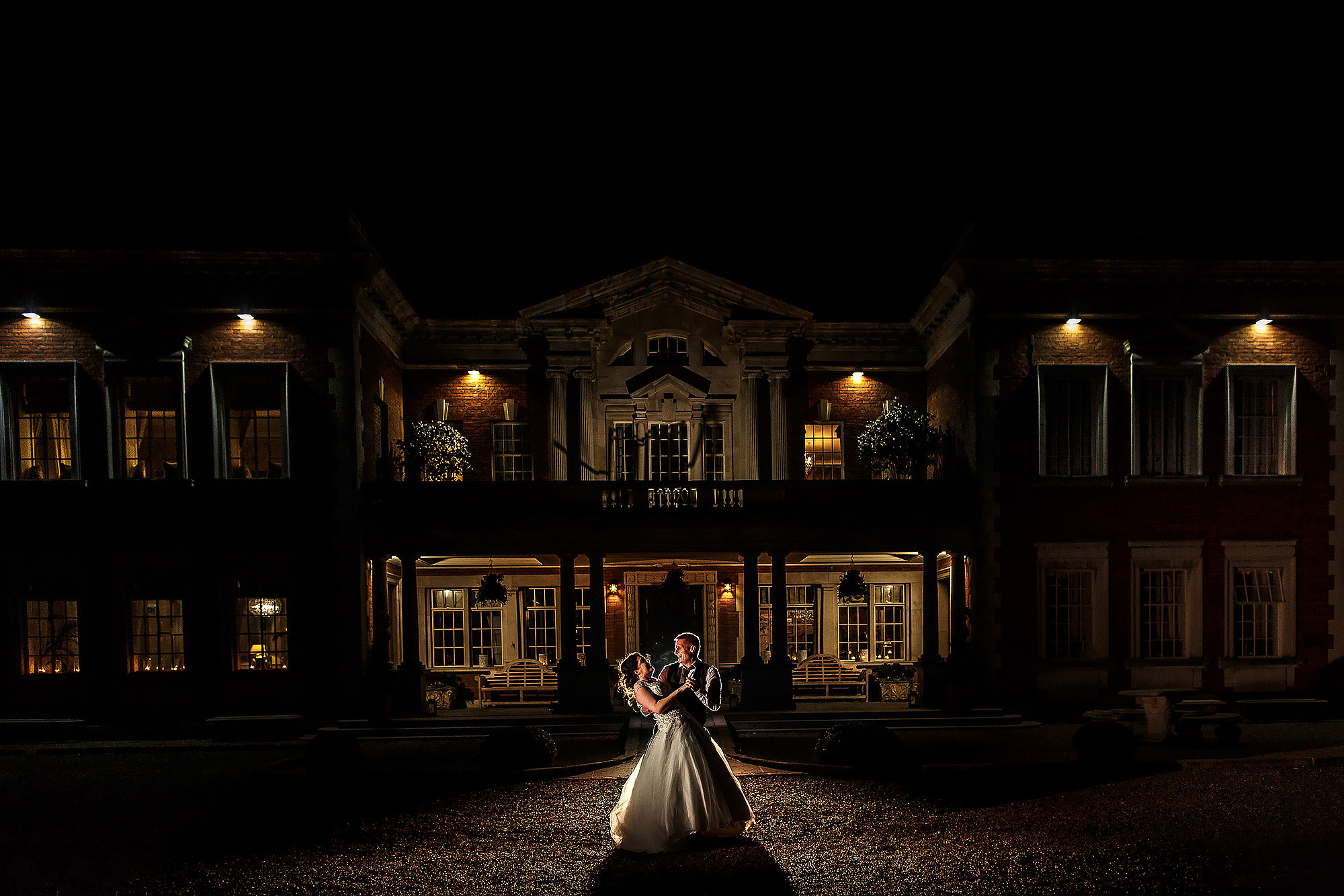 Bride and groom dancing outside Eaves Hall at night with the front of the building lit | Eaves Hall wedding photography by Toni Darcy
