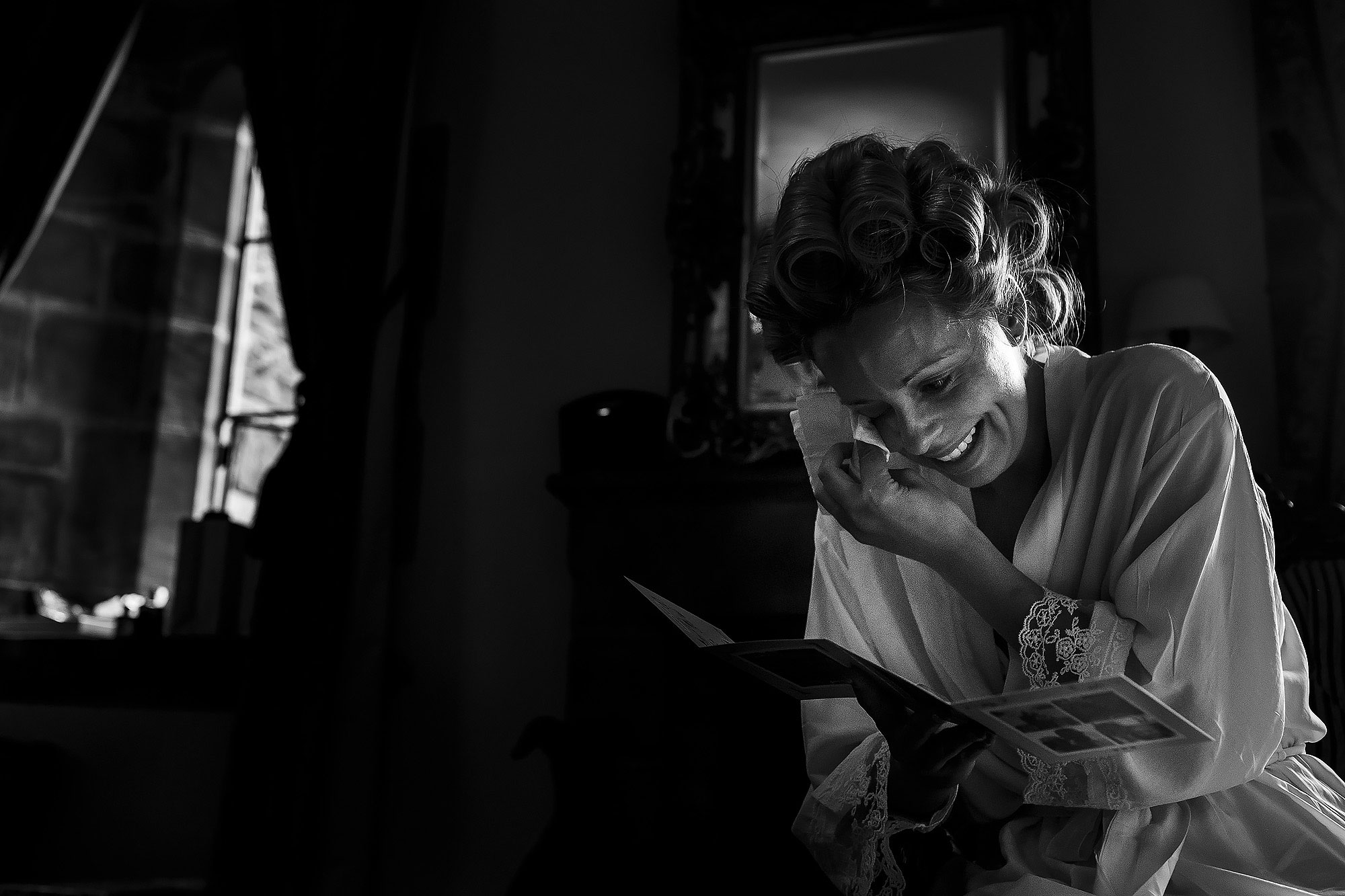 Bride crying holding a tissue to her eyes whilst reading a card on the morning of her wedding day | Peckforton Castle Wedding by Toni Darcy Photography