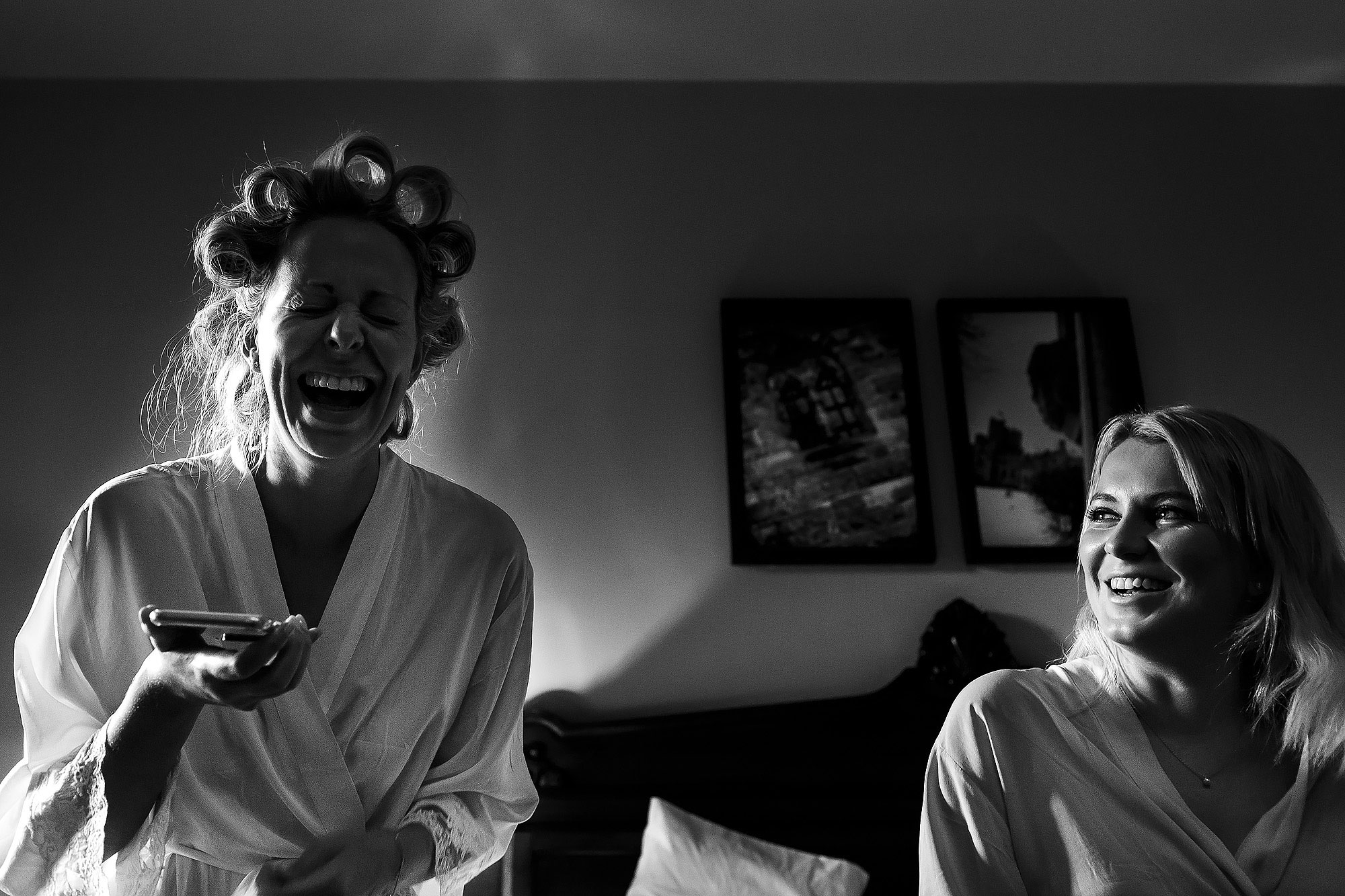Bride and bridesmaids wearing matching dressing gowns laughing | Peckforton Castle Wedding by Toni Darcy Photography