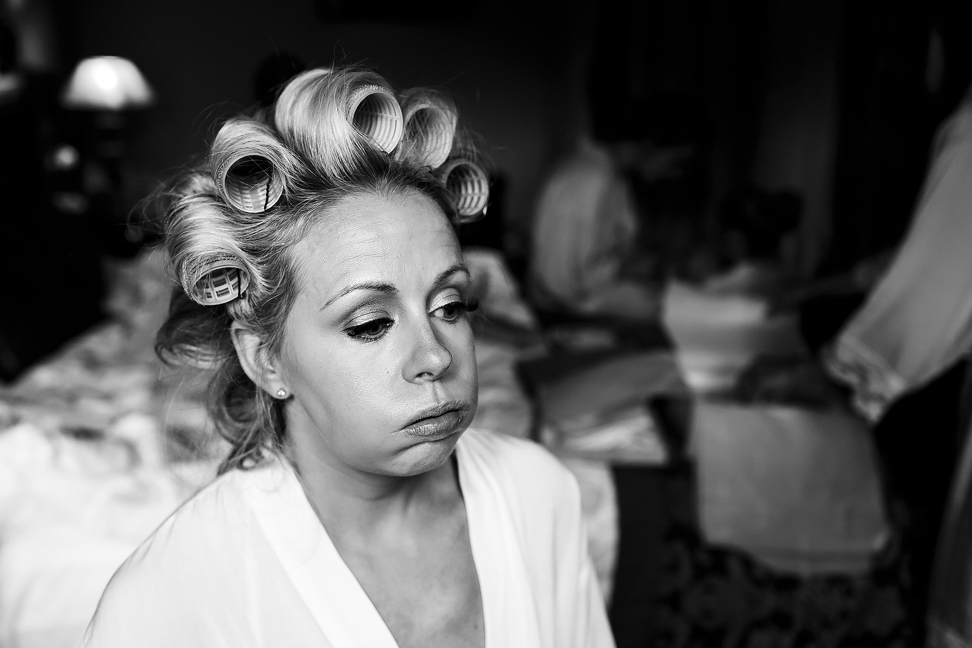 Bride wearing rollers blowing cheeks out in nerves on the morning of her wedding day | Peckforton Castle Wedding by Toni Darcy Photography