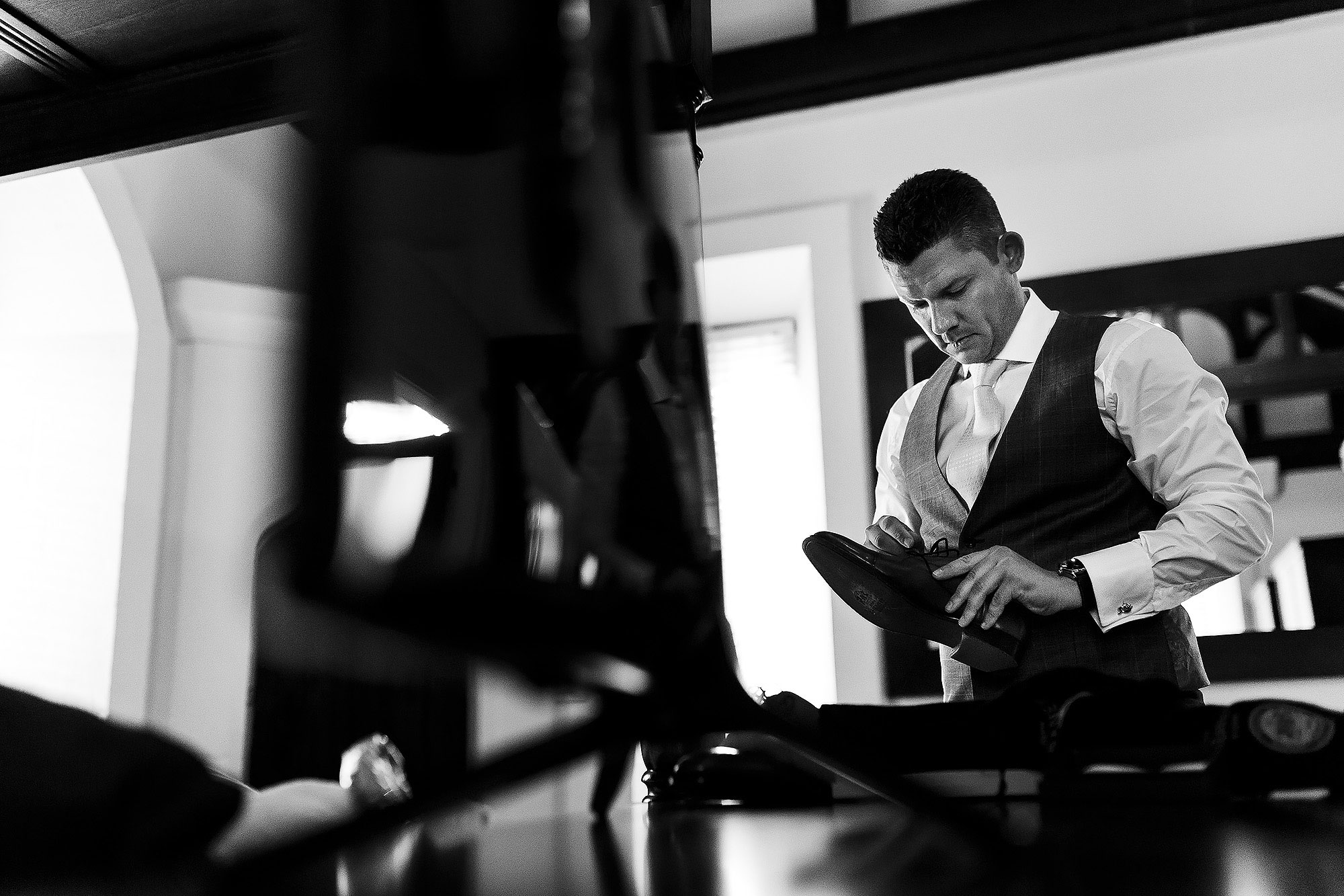 Groom loosening his laces on his shoes on the morning of his wedding | Peckforton Castle Wedding by Toni Darcy Photography