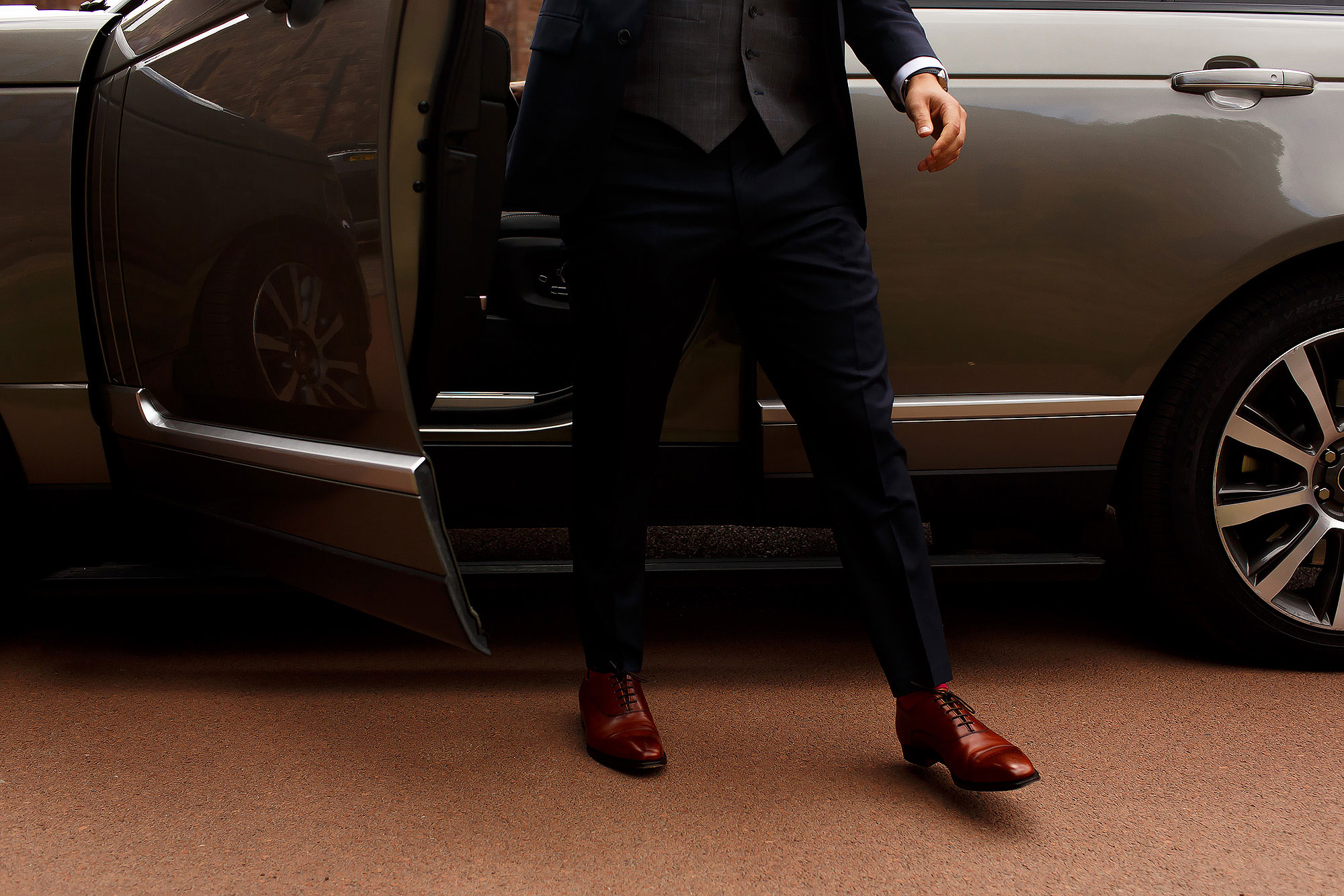 Groom wearing navy suit and brown shoes stepping out of wedding car | Peckforton Castle Wedding by Toni Darcy Photography