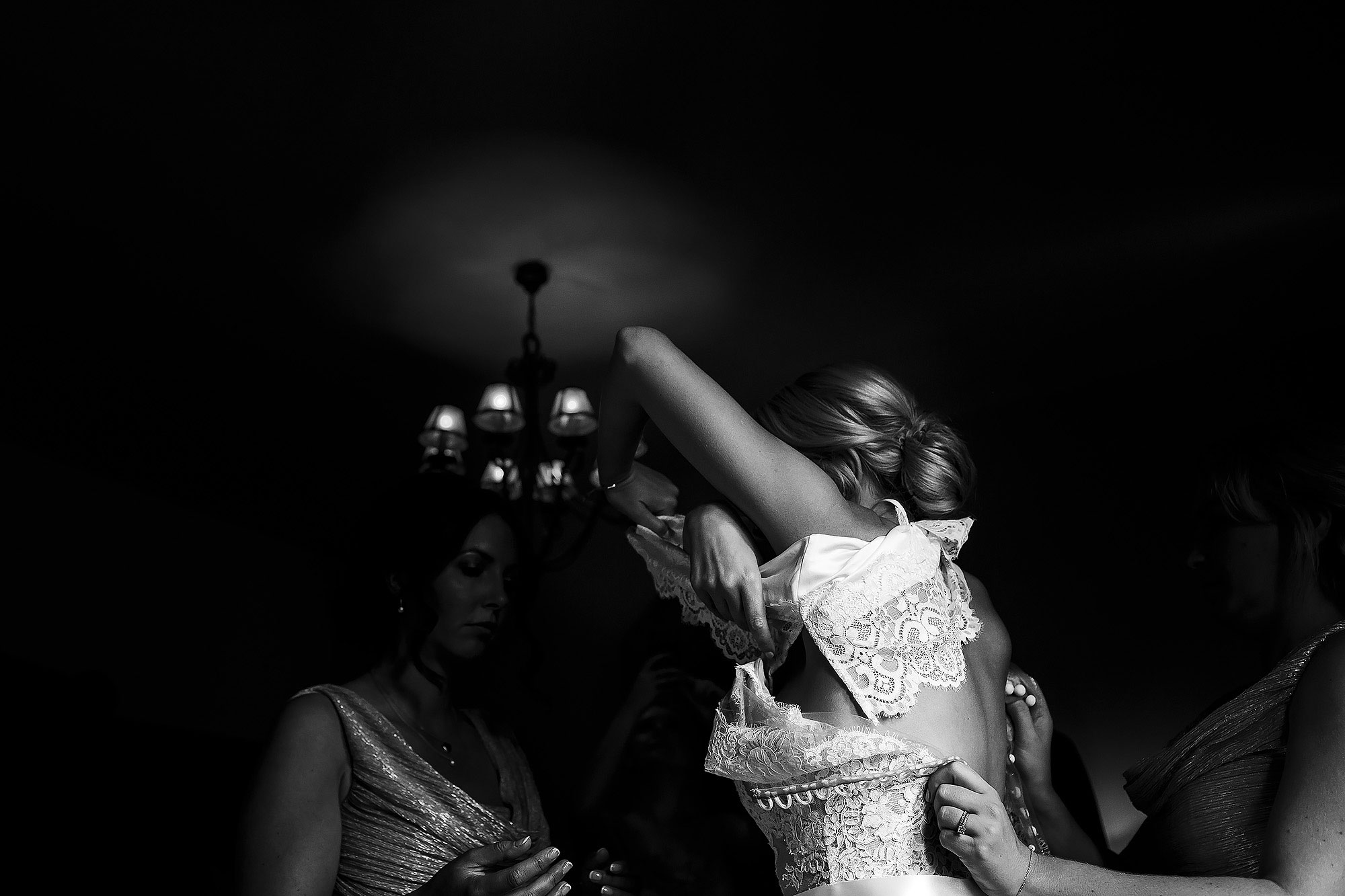 Bride with arms in the air as she steps into wedding dress with lace detail   Peckforton Castle Wedding by Toni Darcy Photography