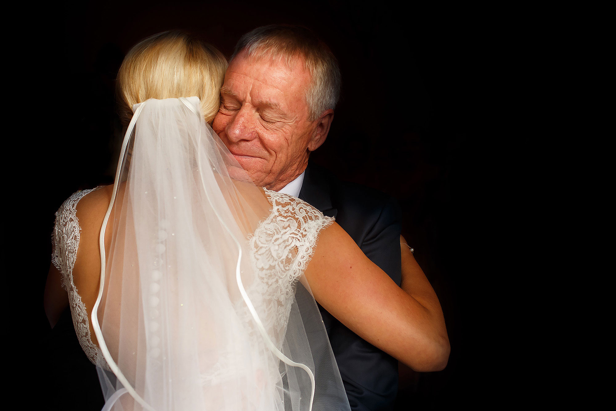 Bride with lace low back wedding dress wearing veil hugging father for the first time | Peckforton Castle Wedding by Toni Darcy Photography