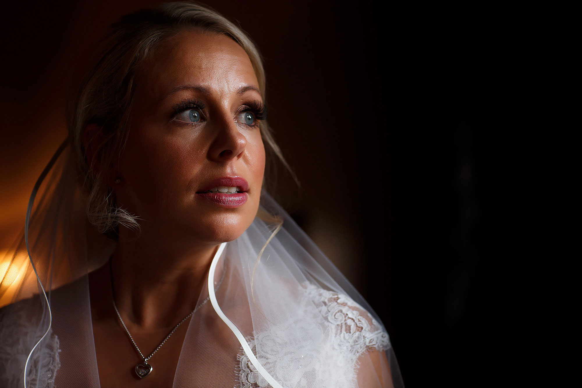 Bride with big blue eyes and blonde hair looking emotional as veil caps shoulders | Peckforton Castle Wedding by Toni Darcy Photography