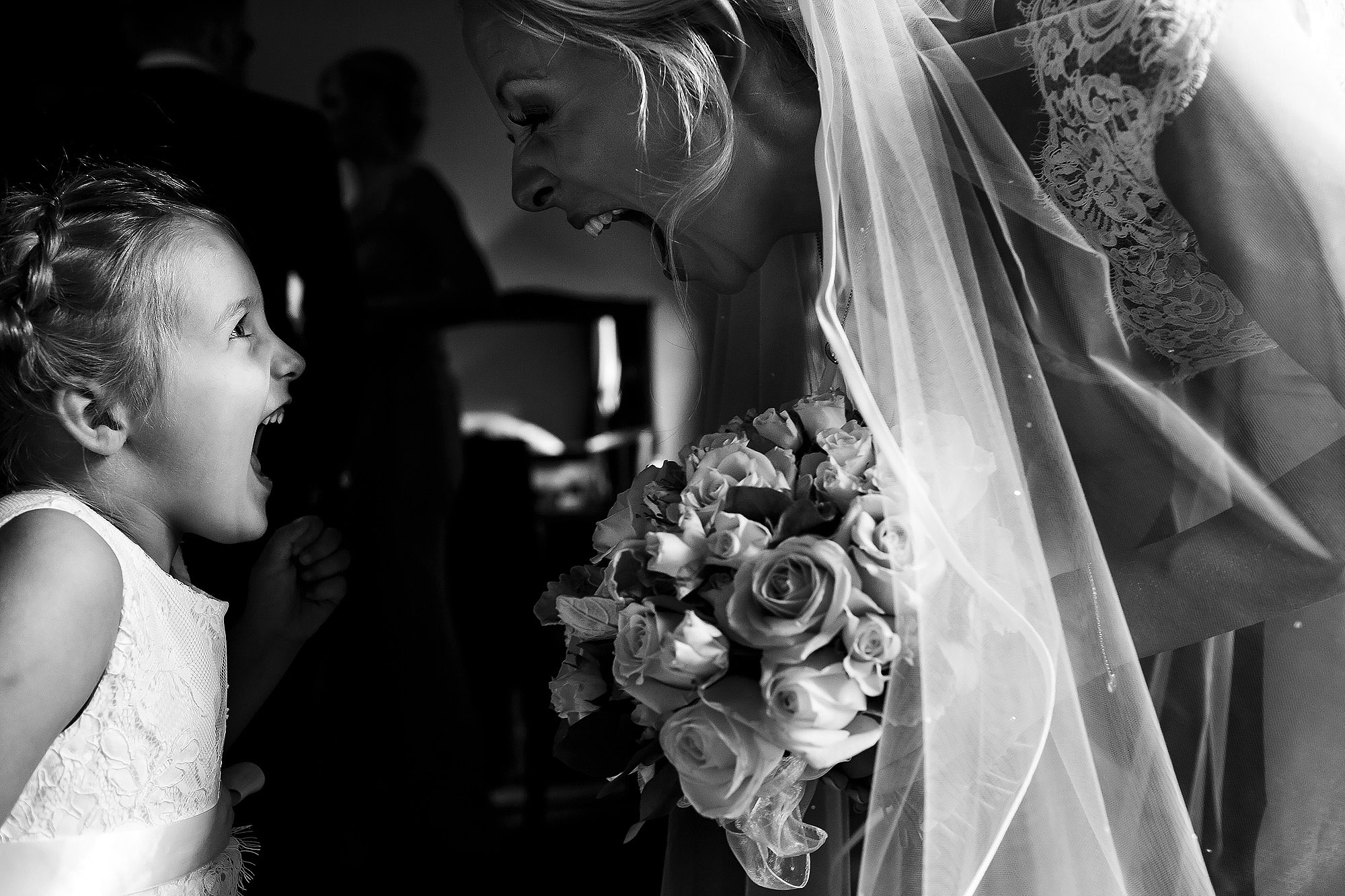 Bride and flower girl holding flowers with mouths open facing each other | Peckforton Castle Wedding by Toni Darcy Photography