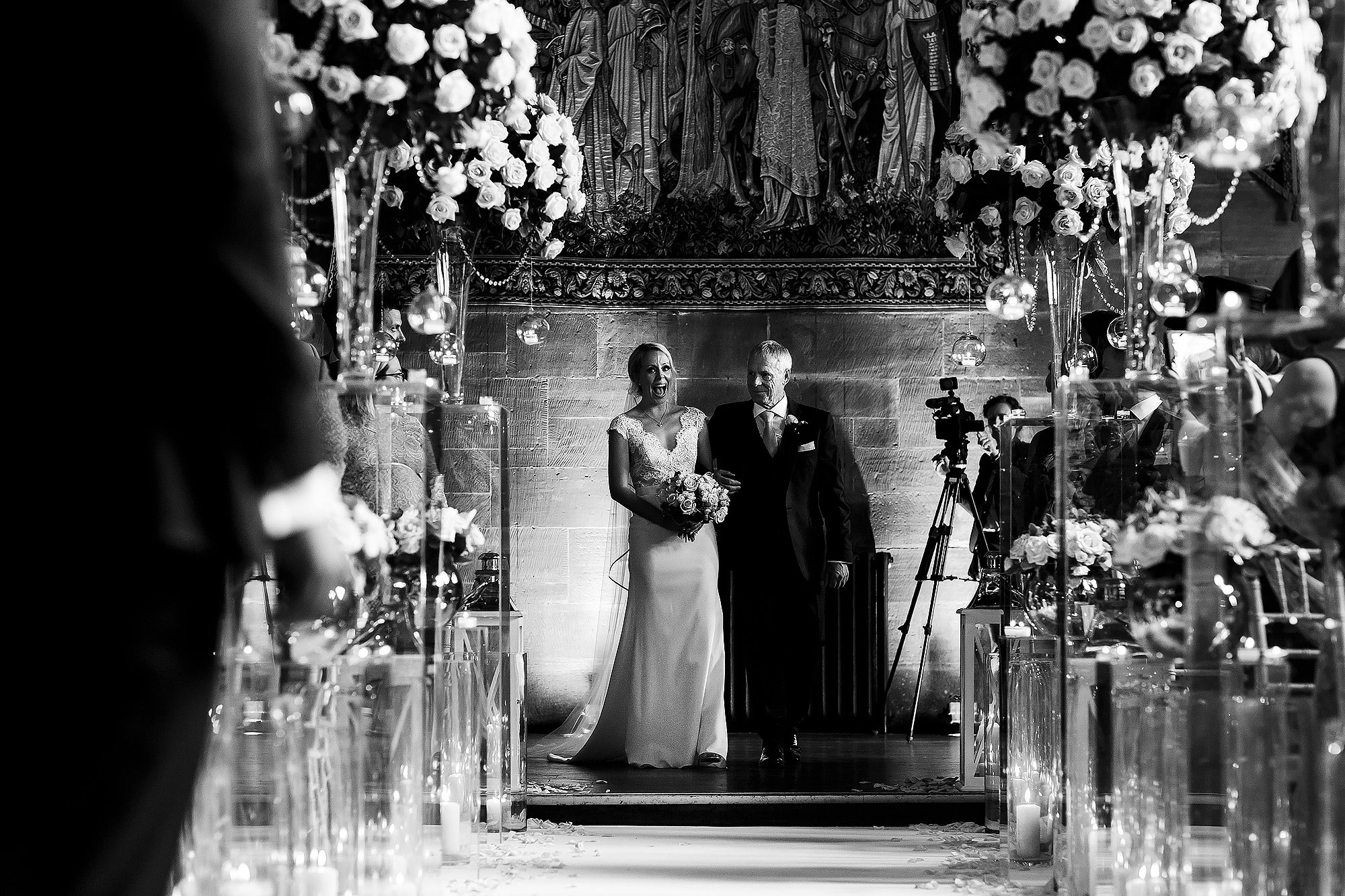 Bride looking excited as shes about to walk down the wedding aisle decorated with large floral display | Peckforton Castle Wedding by Toni Darcy Photography