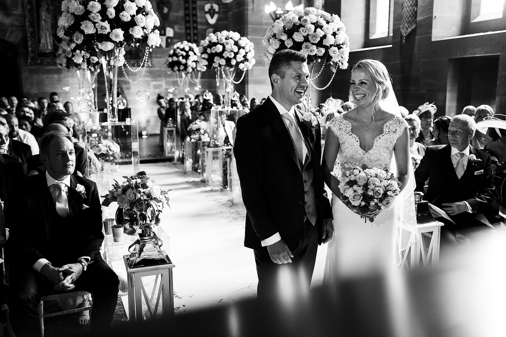 Bride with blonde hair and low bun wearing v neck lace wedding dress smily at the groom as she reaches the top of the wedding aisle | Peckforton Castle Wedding by Toni Darcy Photography