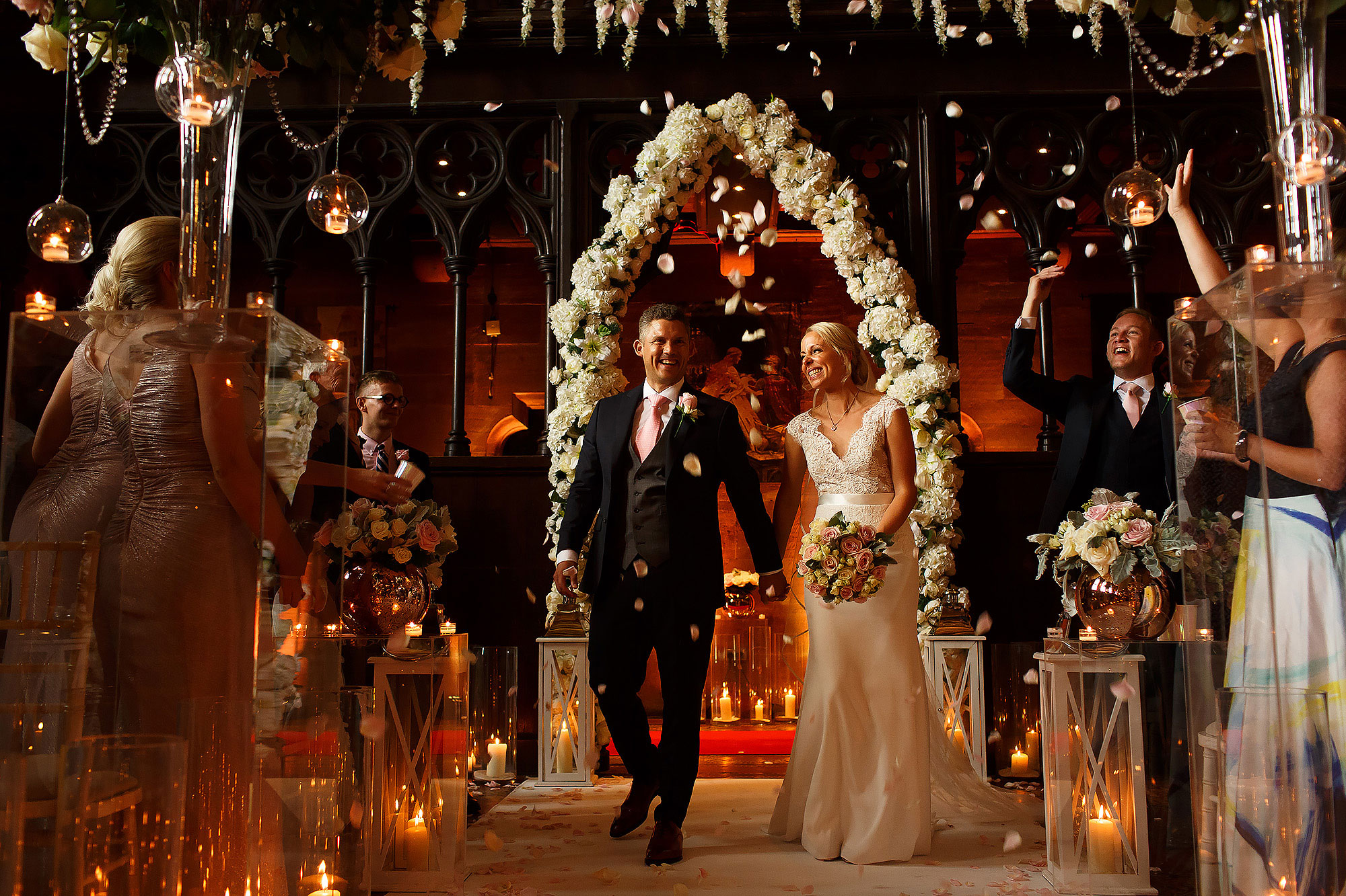 Bride and groom holding hands in the air in front of large floral arch at the top of the wedding aisle decorated with candles and flowers as guests throw wedding confetti | Peckforton Castle Wedding by Toni Darcy Photography