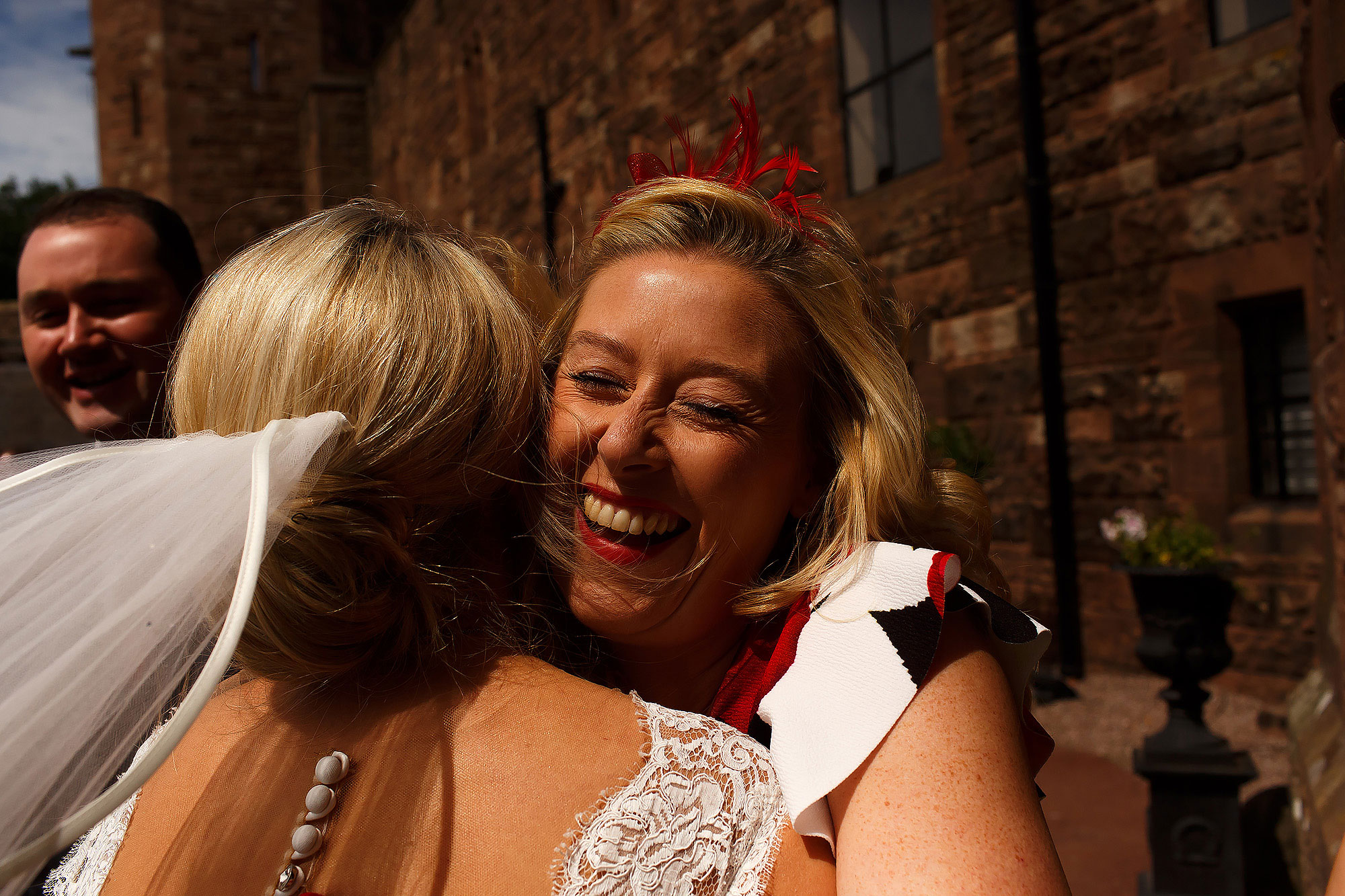Wedding guests hugging the bride at the front of Peckforton Castle | Peckforton Castle Wedding by Toni Darcy Photography