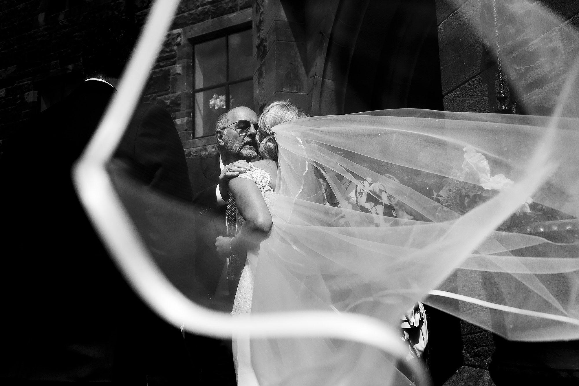 Bride hugging wedding guests outside Peckforton Castle as the veil flows around framing them | Peckforton Castle Wedding by Toni Darcy Photography