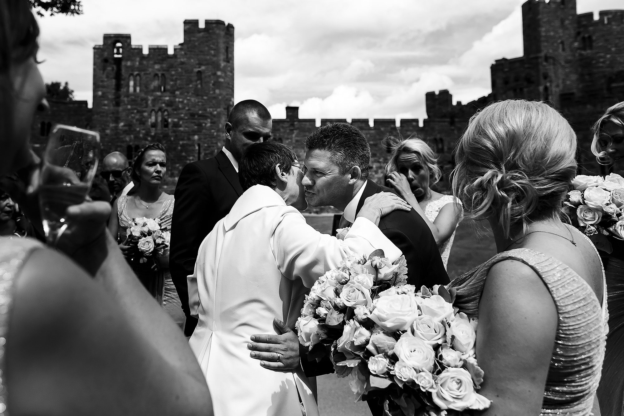 Bride and Groom hugging wedding guests with Peckforton Castle in the background | Peckforton Castle Wedding by Toni Darcy Photography