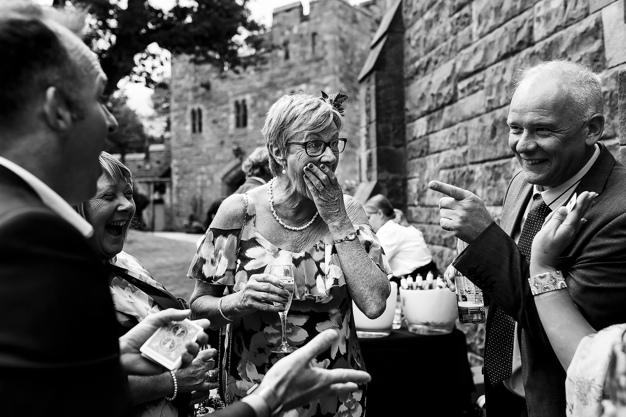 Bride and groom watching magician outside Peckforton Castle | Peckforton Castle Wedding by Toni Darcy Photography