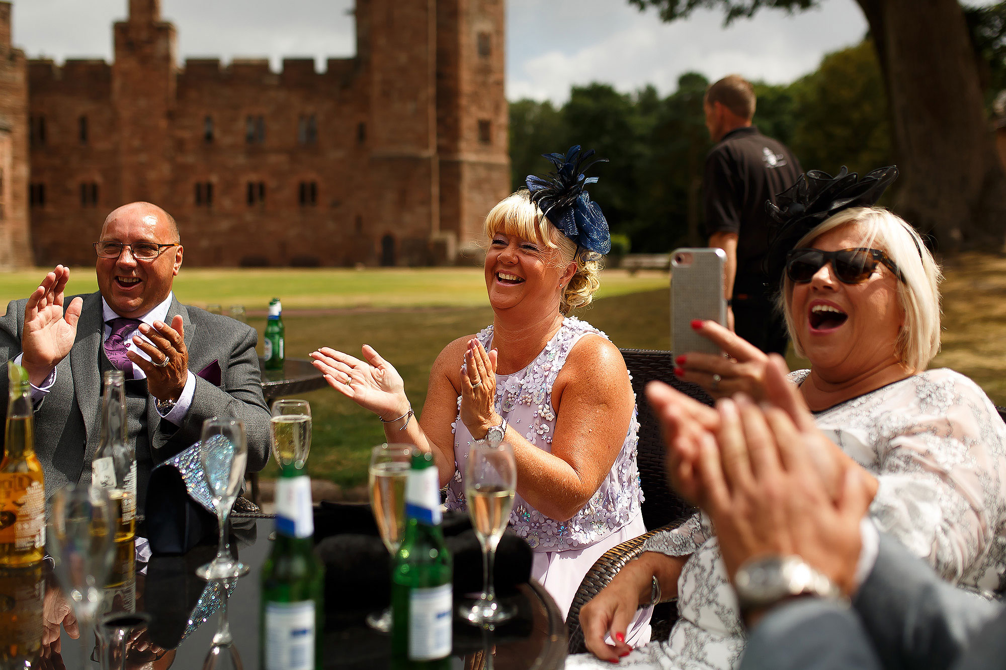 Wedding guests enjoying champagne outside Peckforton Castle | Peckforton Castle Wedding by Toni Darcy Photography