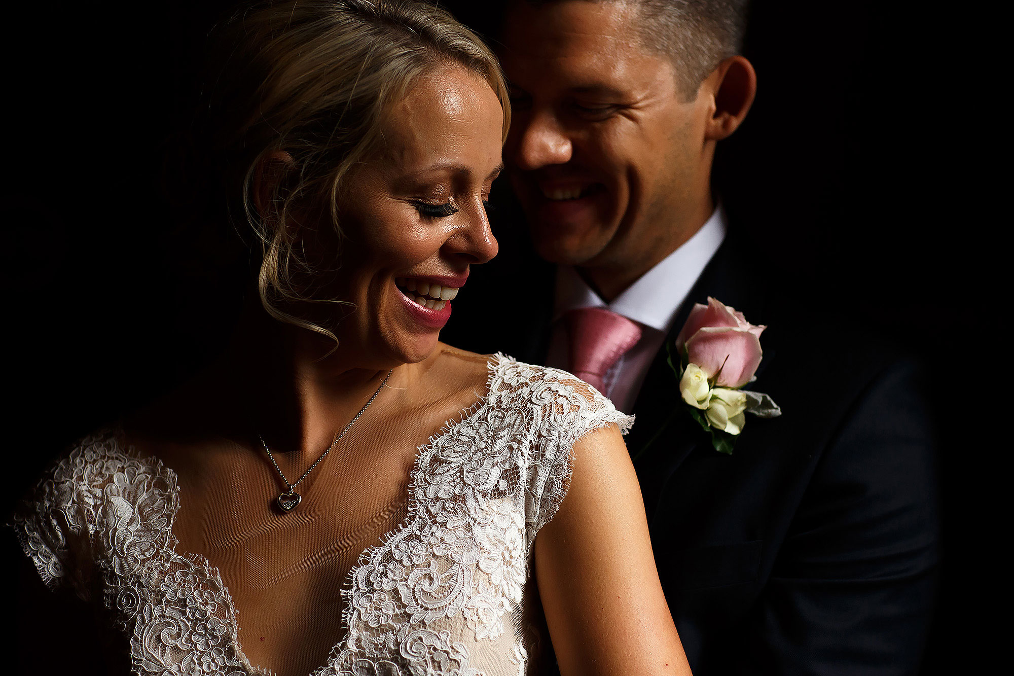 Bride wearing v neck scalloped lace wedding dress with blonde hair as groom wearing pink button hole hugs her from behind | Peckforton Castle Wedding by Toni Darcy Photography