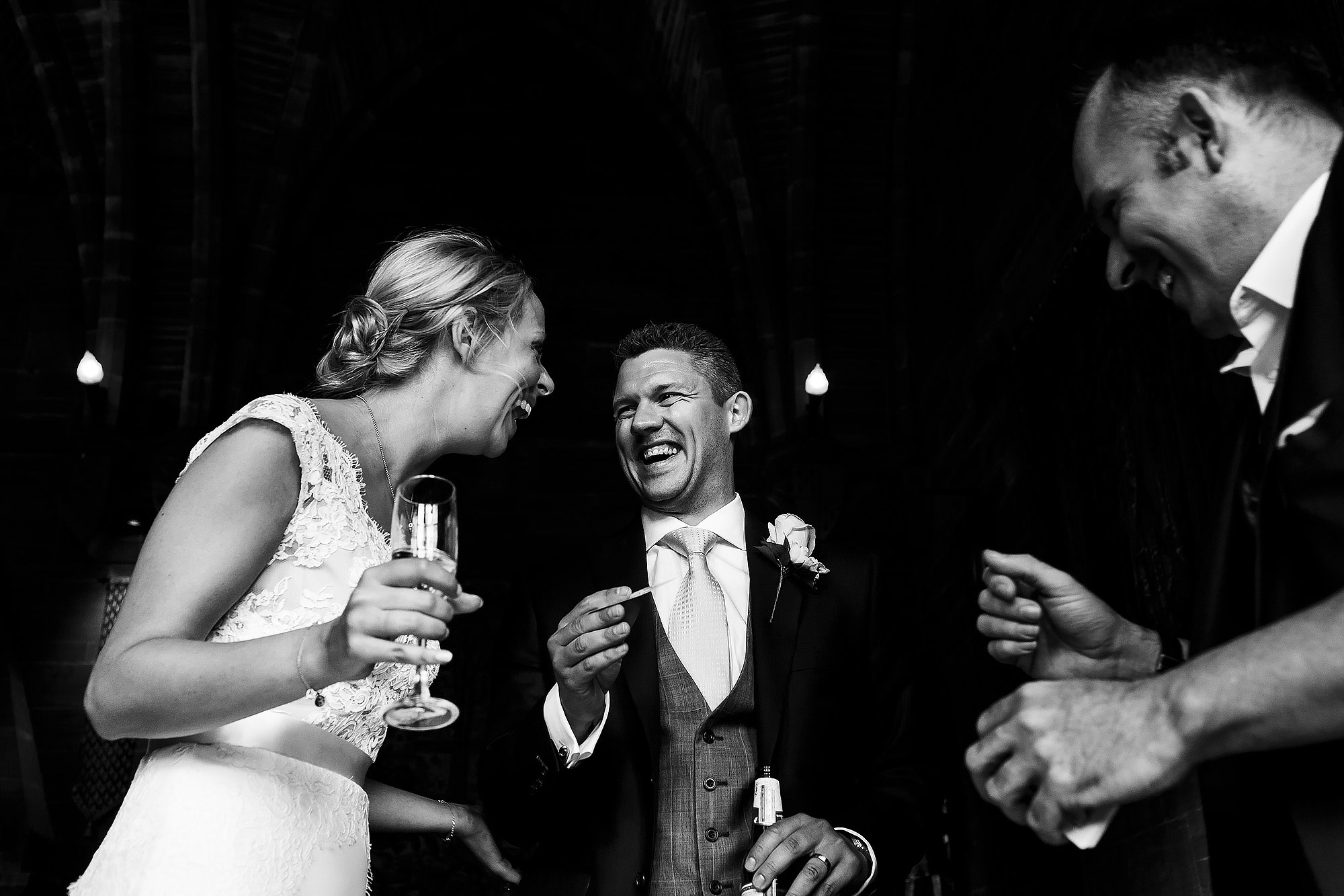 Bride and groom laughing as magician shows them a trick | Peckforton Castle Wedding by Toni Darcy Photography