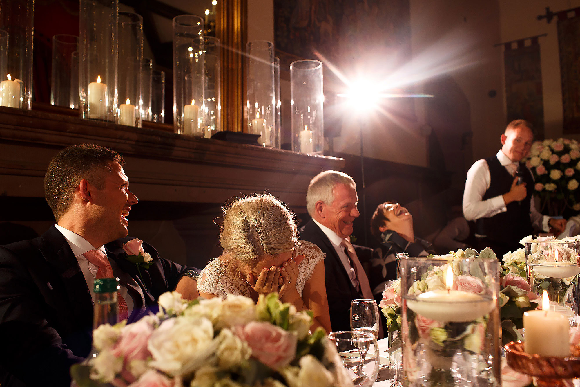 Top table laughing during wedding speeches with decorations of flowers and candles | Peckforton Castle Wedding by Toni Darcy Photography