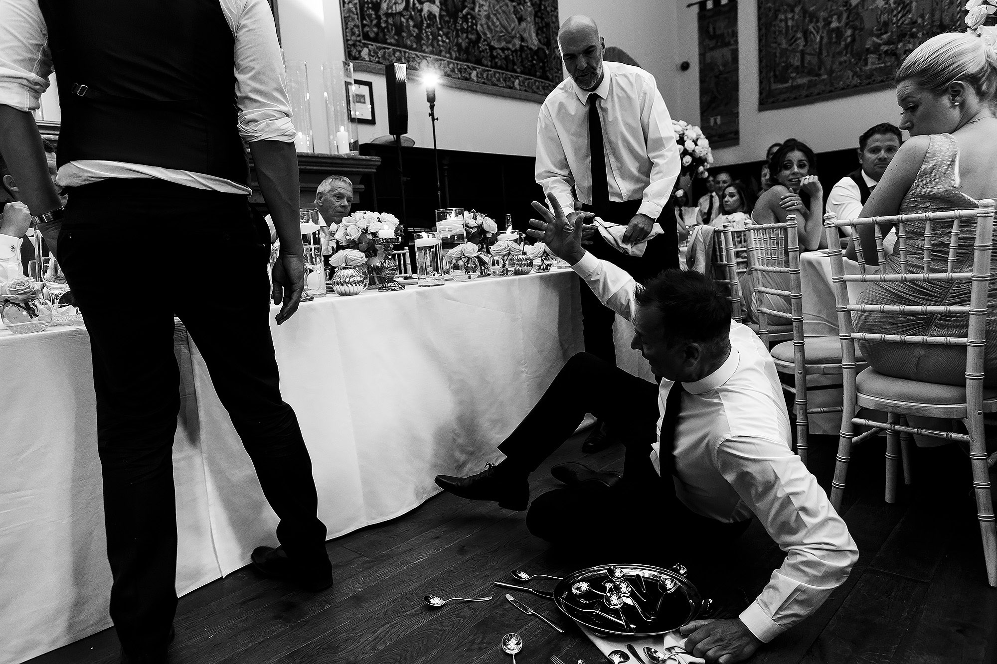 Singing waiters drop a tray of cutlery to create commotion in front of the top table | Peckforton Castle Wedding by Toni Darcy Photography