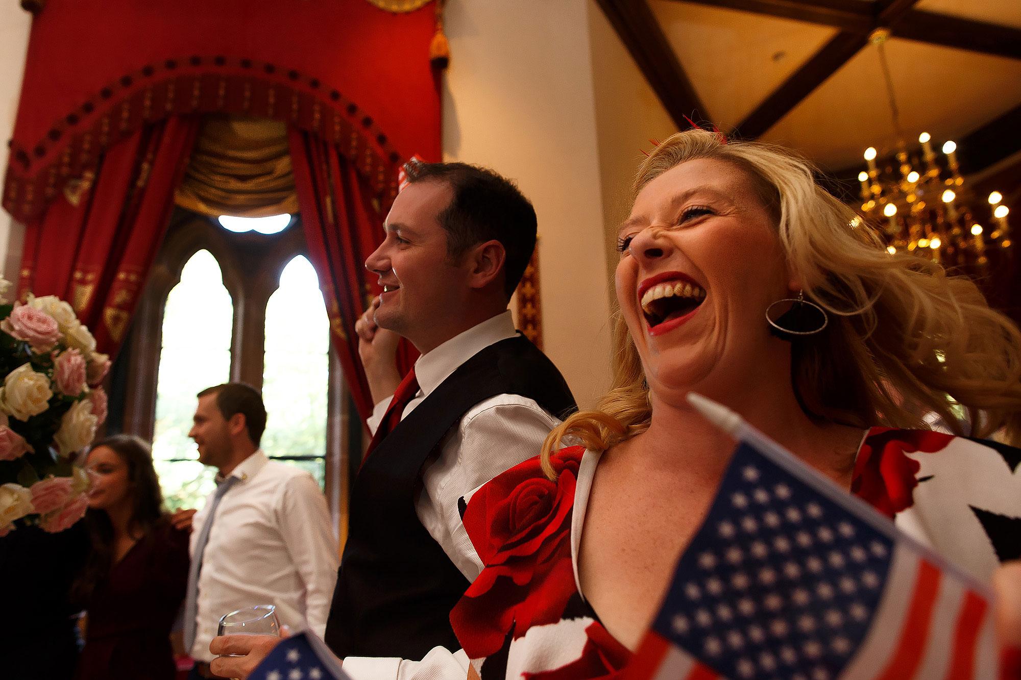 Wedding guests dancing waving flags | Peckforton Castle Wedding by Toni Darcy Photography