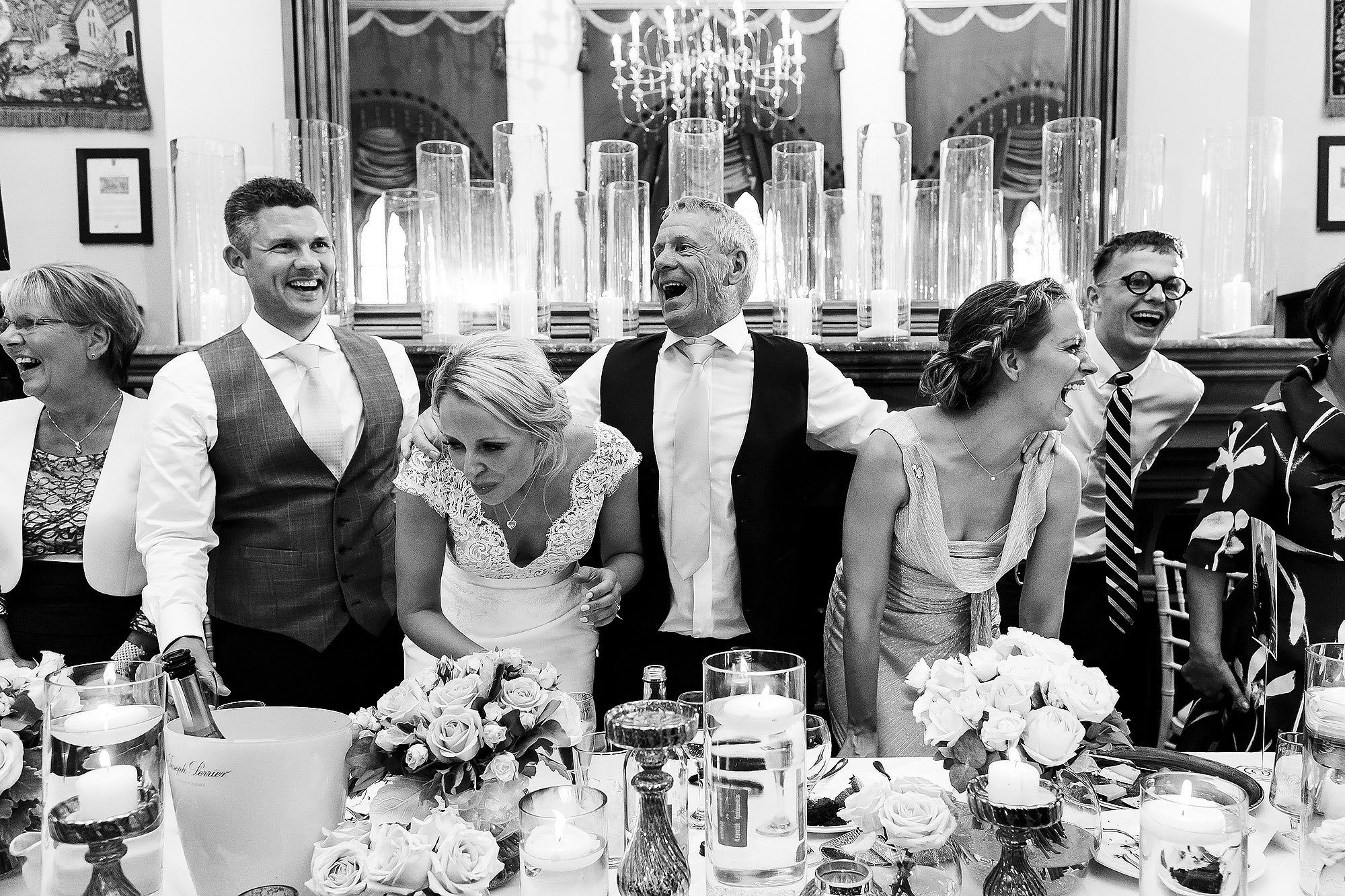 Top table dancing behind the table during drinks reception | Peckforton Castle Wedding by Toni Darcy Photography