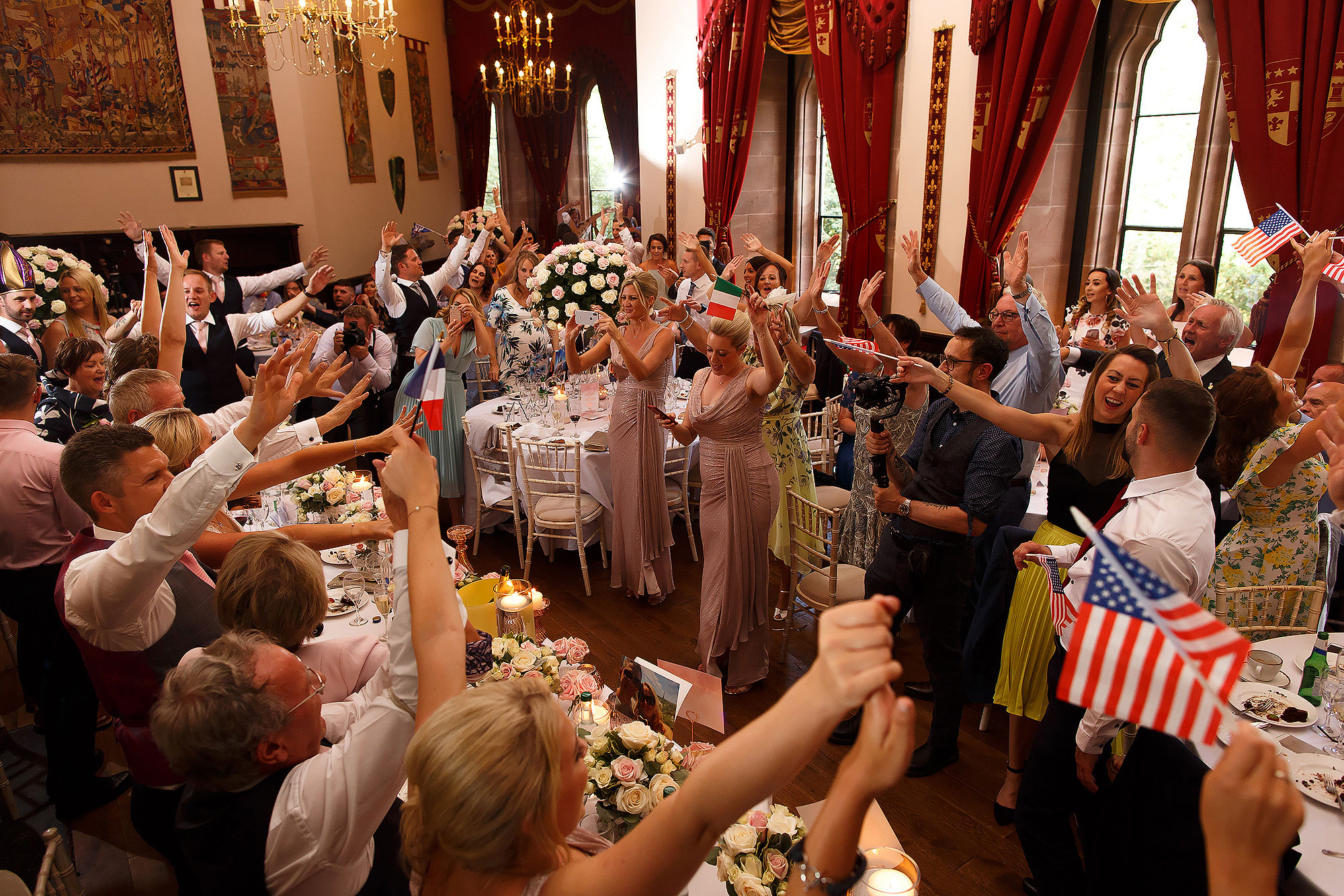 Full wedding party dancing, singing and waving flags during wedding reception of singing waiters | Peckforton Castle Wedding by Toni Darcy Photography