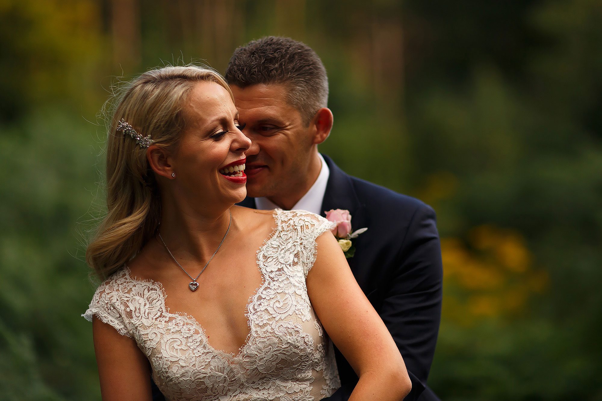 Bride wearing lace wedding dress and side hair clip facing groom wearing blue suit in the forest at Peckforton Castle | Peckforton Castle Wedding by Toni Darcy Photography