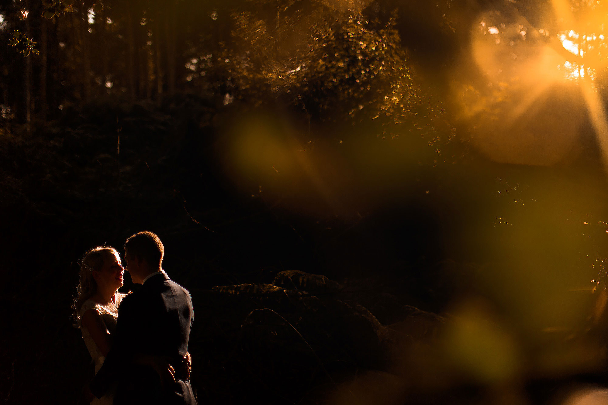 Bride and groom facing each other with sun flare during golden hour in the forest | Peckforton Castle Wedding by Toni Darcy Photography