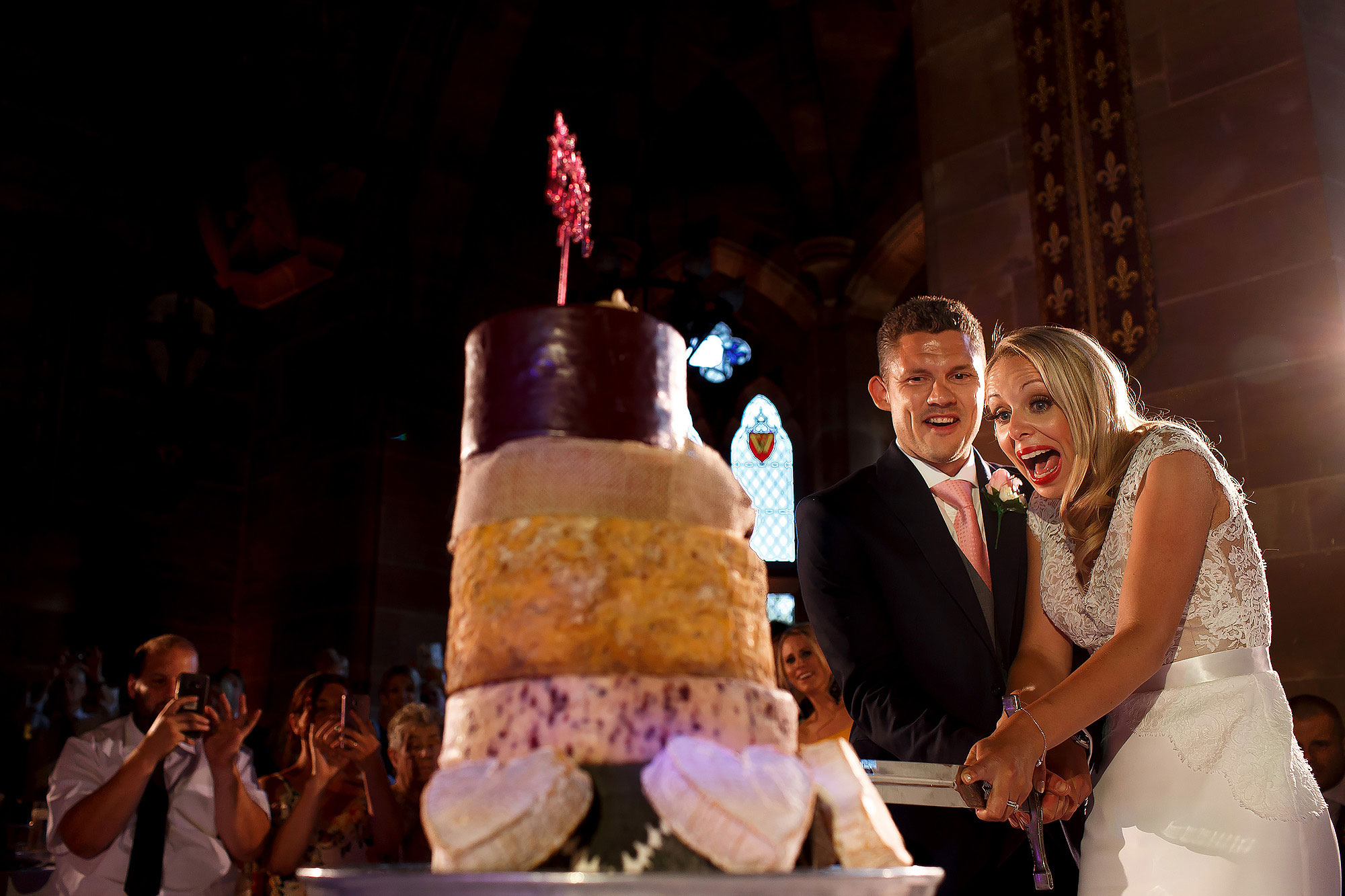 Bride and groom cutting 5 tier cheese wedding cake with sword at Peckforton Castle | Peckforton Castle Wedding by Toni Darcy Photography