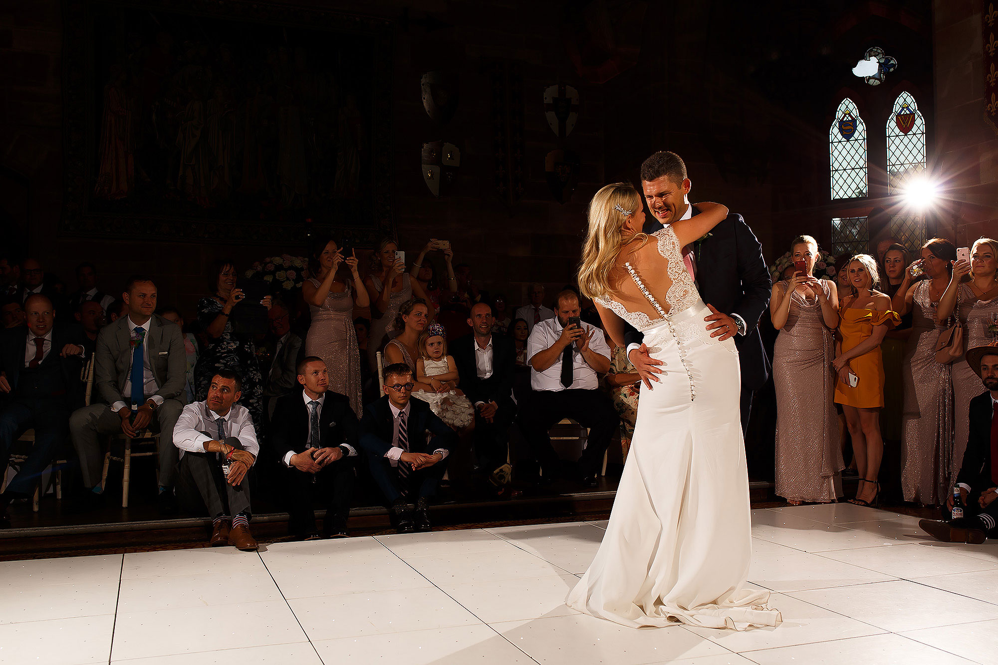 Bride and groom on the white dance floor holding each other during first dance as wedding guests all watch | Peckforton Castle Wedding by Toni Darcy Photography